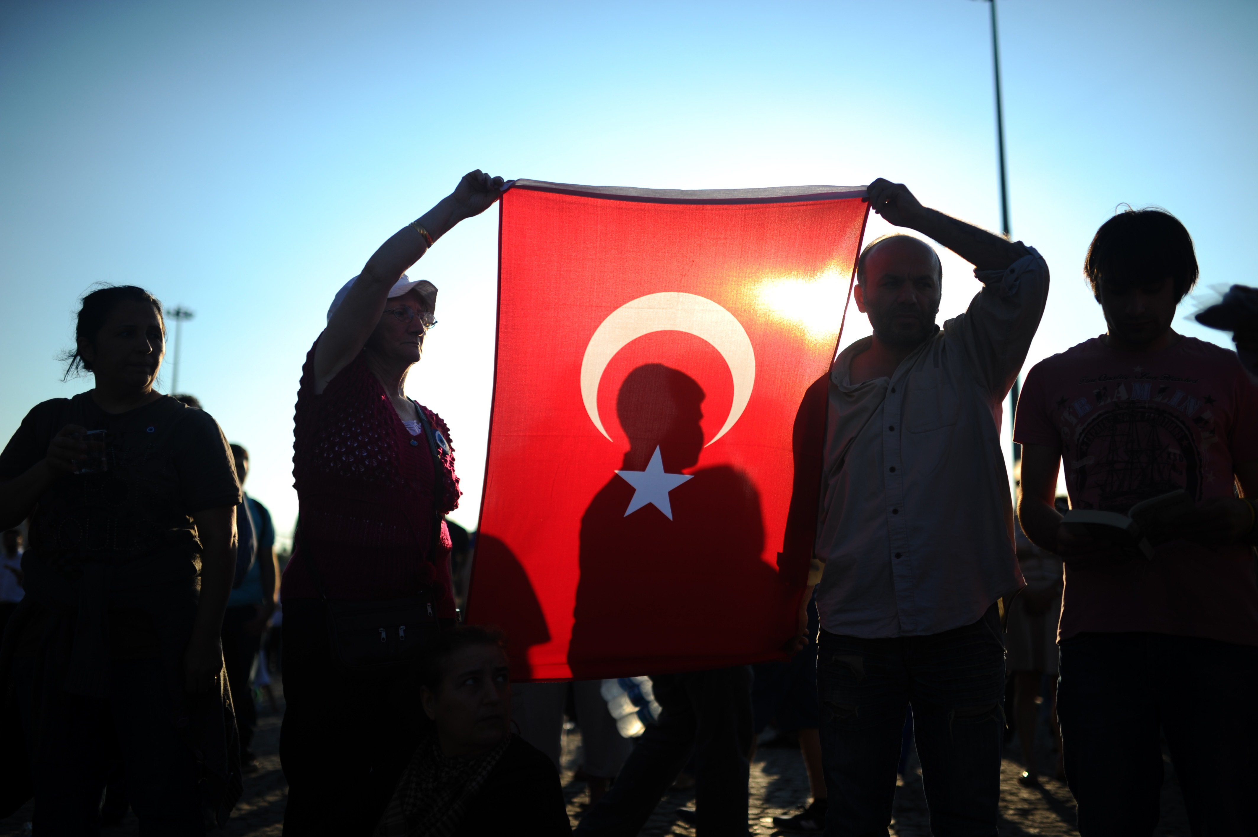 People hold a Turkish national flag as they stand on the flashpoint Taksim square in Istanbul on June 18, 2013 during a wave of new alternative protests. (AFP Photo)