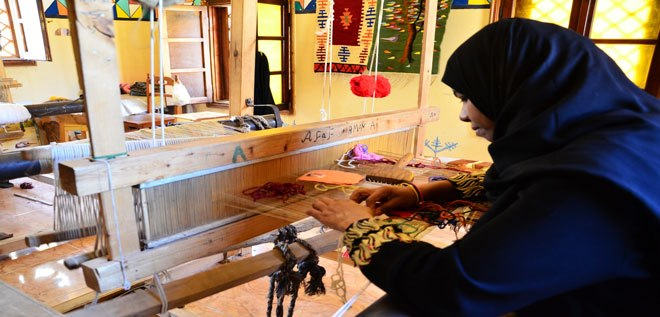 A young Nubian girl working on a traditional loom (Photo from Yadaweya Facebook page)