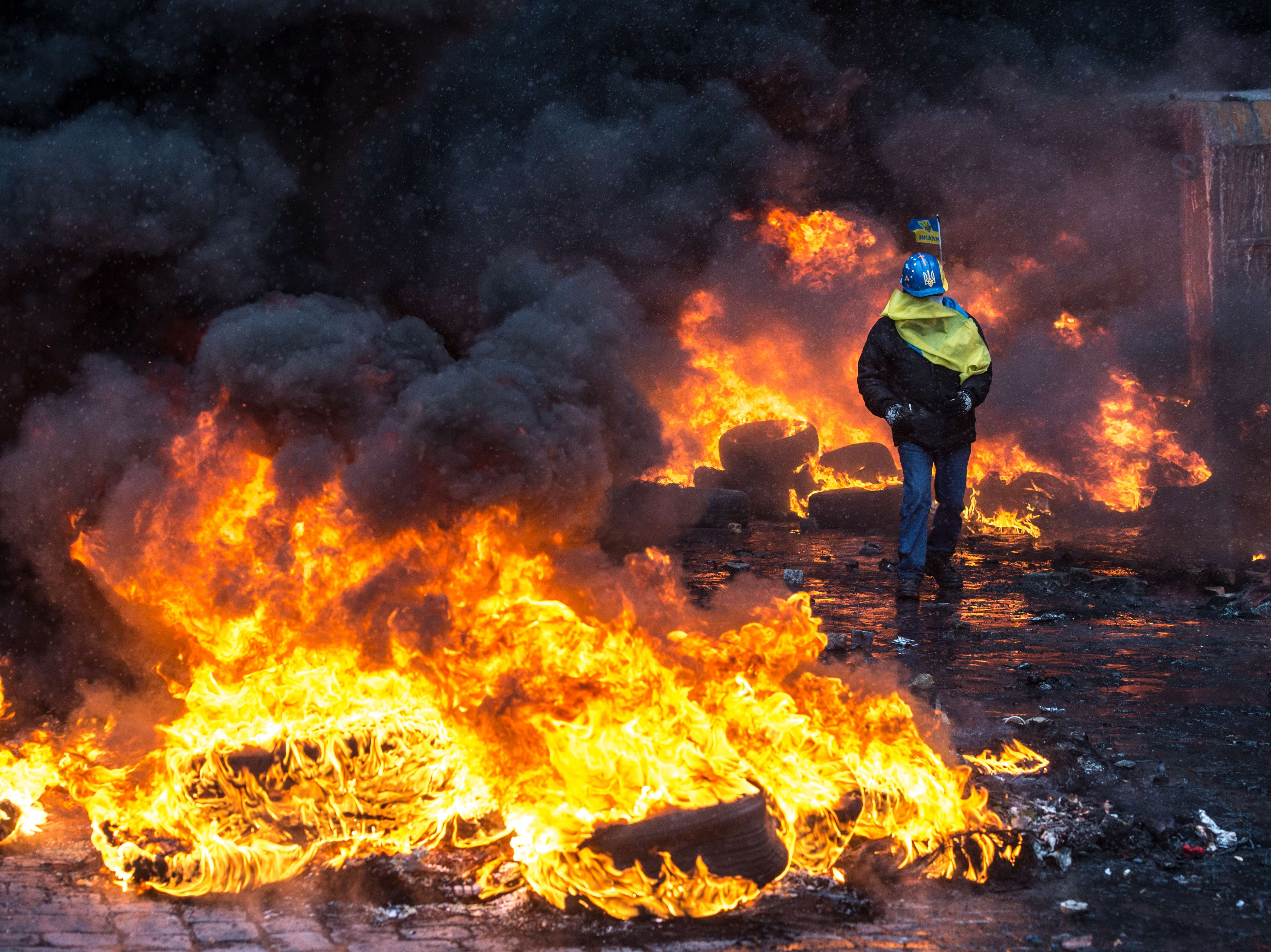 A protestor walks in the near burning tyres during clashes with riot police in Kiev on January 22, 2014. At least two activists were shot dead today as Ukrainian police stormed protesters' barricades in Kiev, the first fatalities in two months of anti-government protests. Pitched battles raged in the centre of the Ukrainian capital as protesters hurled stones at police and the security forces responded with tear gas and rubber bullets.  (AFP PHOTO/ DMITRY SEREBRYAKOV)