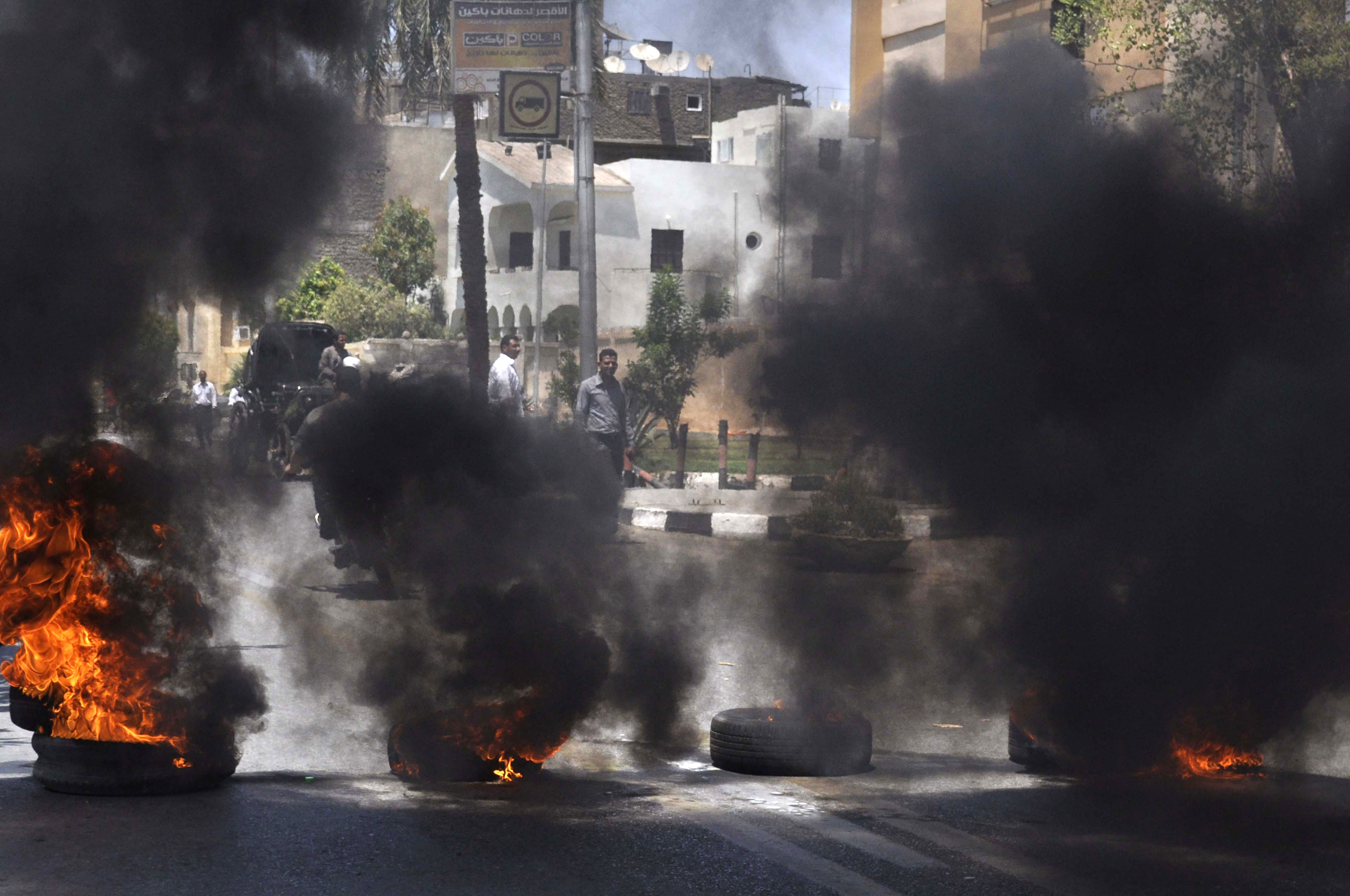 Black smoke rises from tires set on fire by demonstrators outside the Luxor town house protesting against the appointment of Adel al-Khayat, a member of the political arm of ex-Islamic militant group Gamaa Islamiya, as new governor on June 19, 2013 in Luxor, Egypt (AFP Photo)