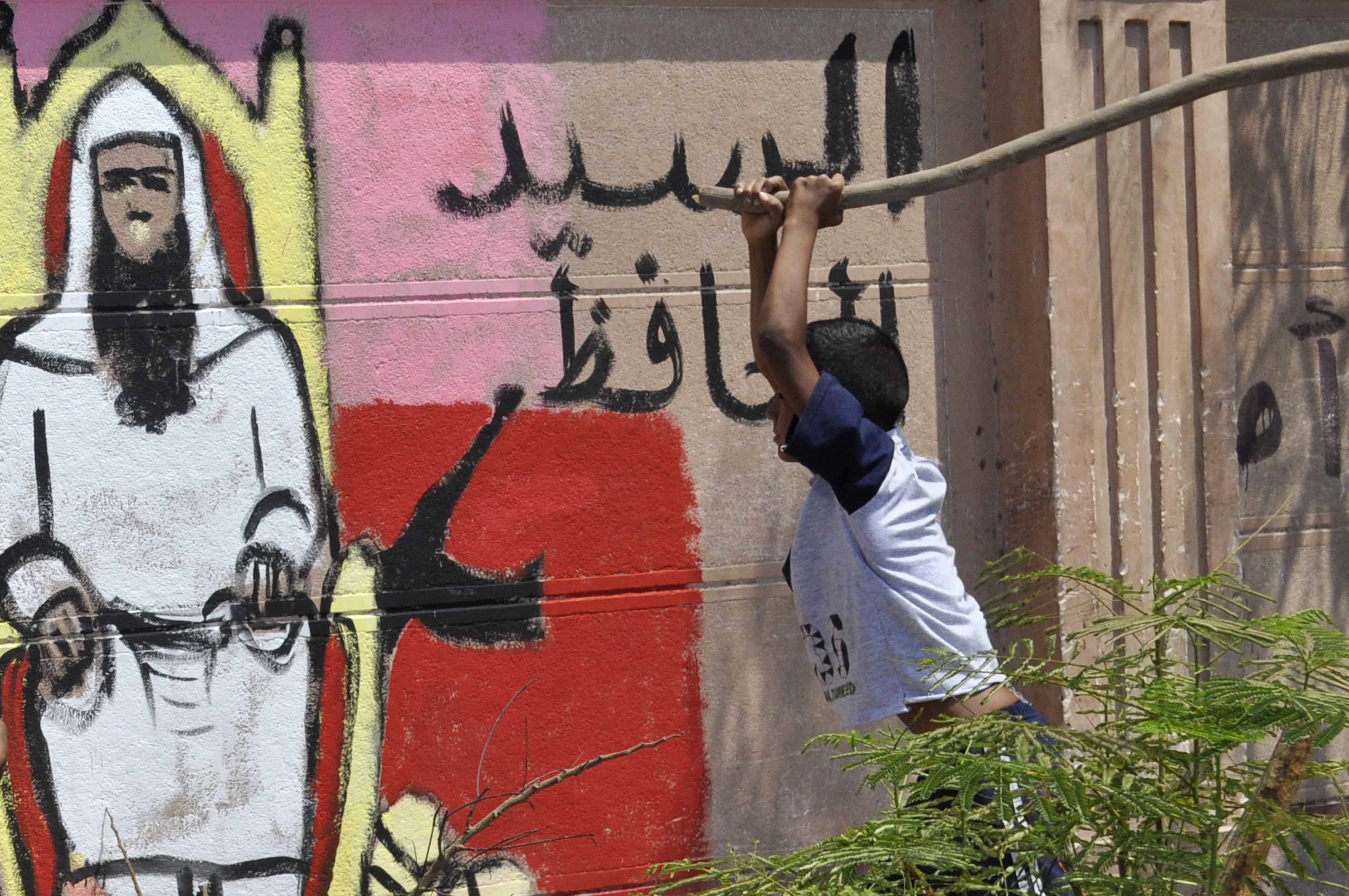 An Egyptian child tries uses a stick to beat a graffiti portraying an Islamist during protest against the appointment of Adel al-Khayat, a member of the political arm of ex-Islamic militant group Gamaa Islamiya, as new governor of Luxor, on June 19, 2013.  (AFP Photo)