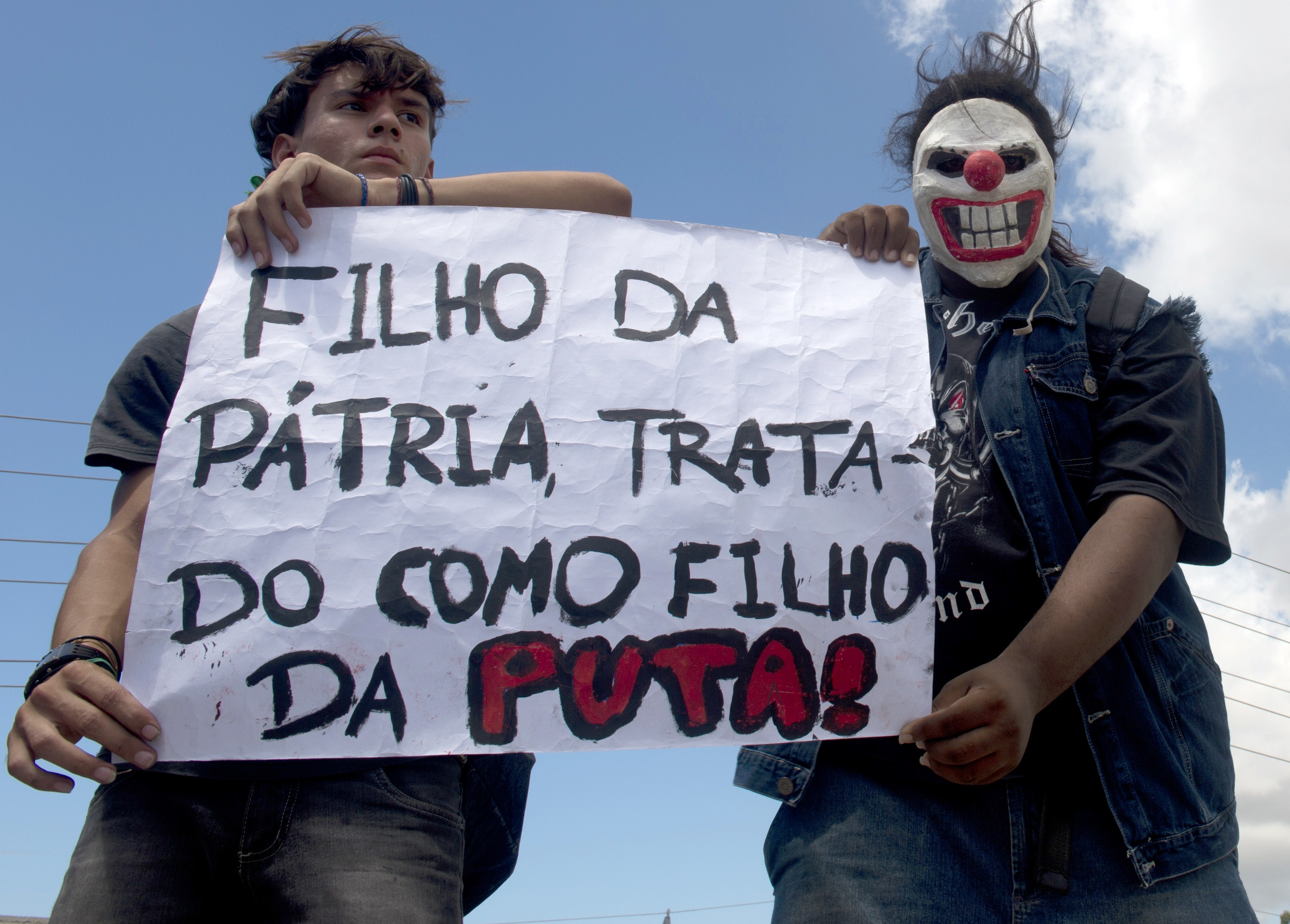 """Protesters hold a poster reading """"Son of the Motherland Treated as Son of a Bitch"""" as a group clashes with the riot police while trying to block access to the Castelao Stadium in Fortaleza, where Brazil is to play Mexico in a FIFA Confederations Cup Brazil 2013 football match, to denounce the events' $15 billion price-tag, on June 19, 2013. (AFP Photo)"""