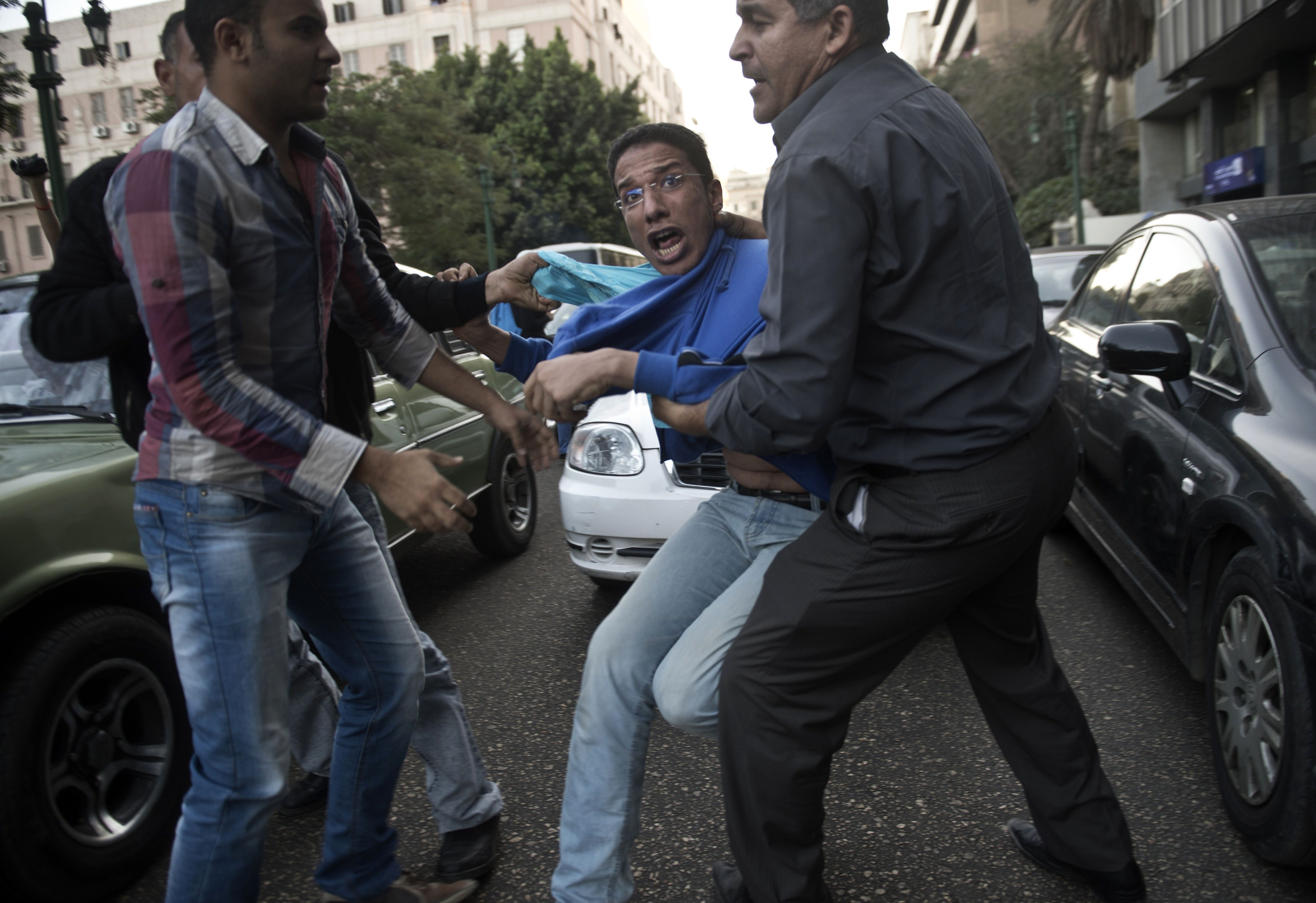 "gyptian policemen in plain clothes detain a protester during a demonstration organized by the group ""No Military Trials for Civilians"" in front of the Shura council in downtown Cairo on November 26, 2013 in the first unauthorised protest staged in the capital since the adoption of a law that regulates demonstrations. (AFP PHOTO / KHALED DESOUKI)"