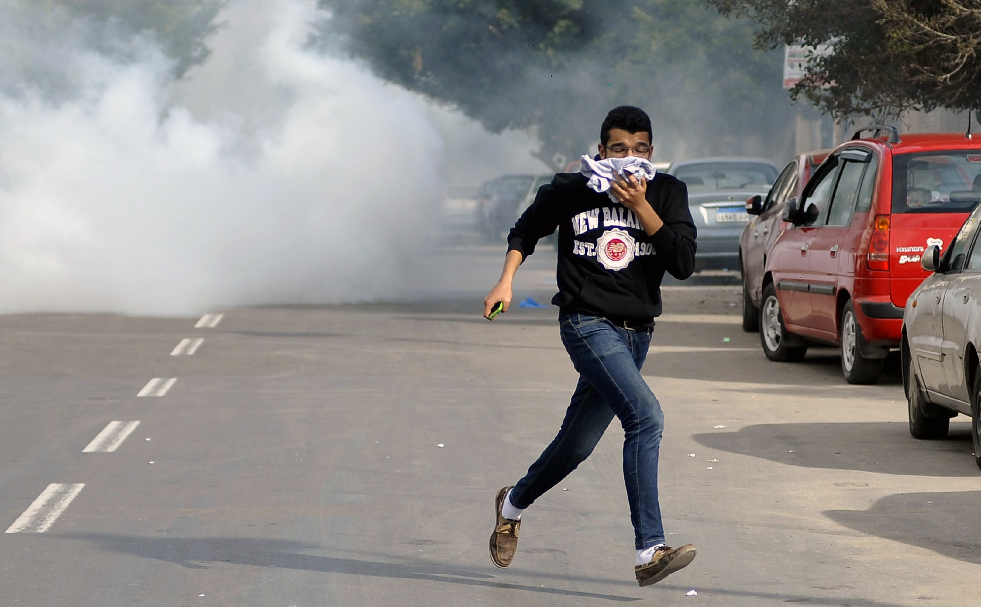 An Egyptian supporter of the Muslim Brotherhood escapes from tear gas during clashes with Egyptian police in the northern port city of Alexandria on January 23, 2014. Clashes between rival Egyptian students at a university in Alexandria killed at least one student, a supporter of ousted Islamist president Mohamed Morsi, police said.  (AFP PHOTO/STR)