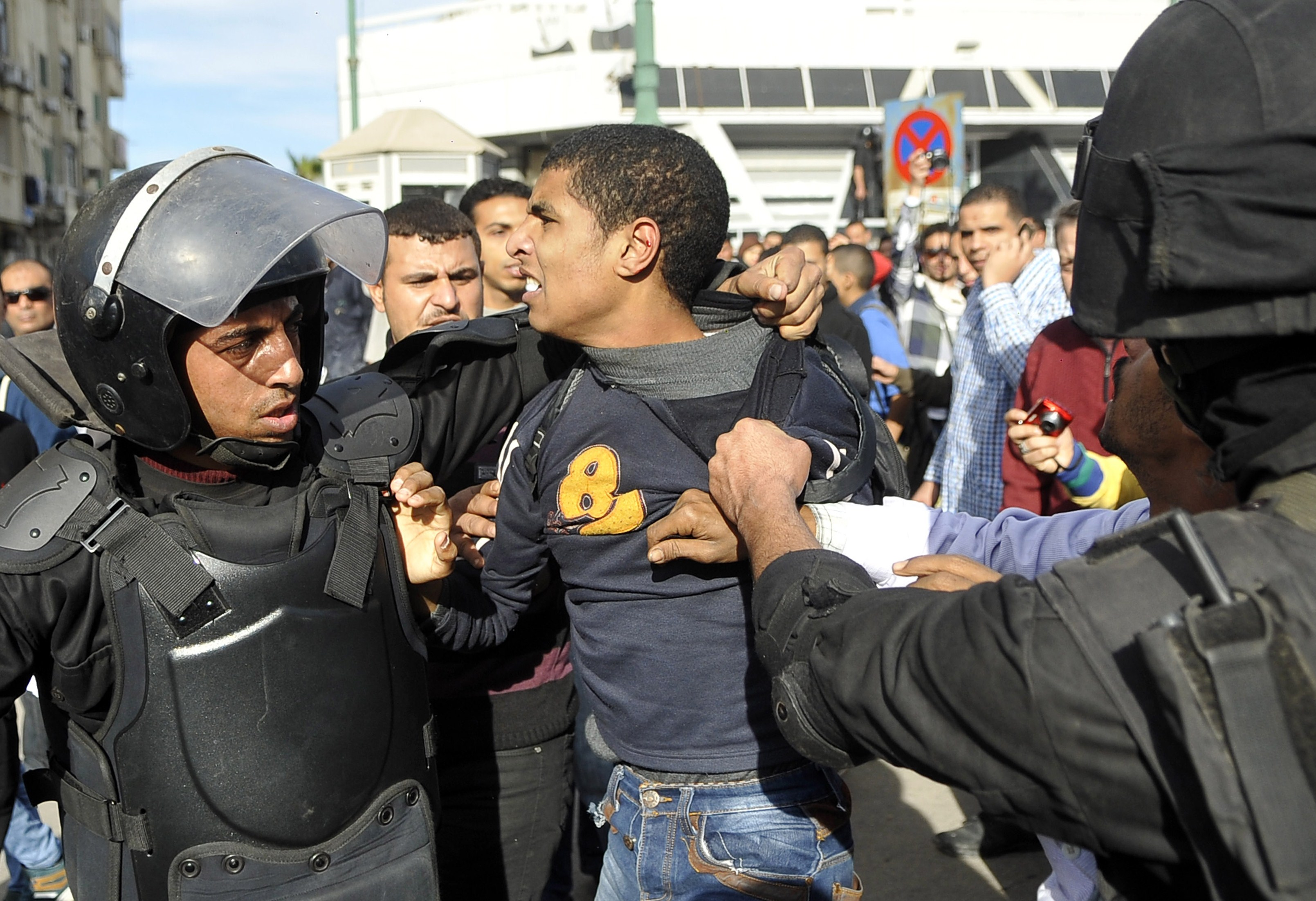 Egyptian police detain a supporter of the Muslim Brotherhood during clashes in the northern port city of Alexandria on January 23, 2014. Clashes between rival Egyptian students at a university in Alexandria killed at least one student, a supporter of ousted Islamist president Mohamed Morsi, police said.  (AFP PHOTO/STR)