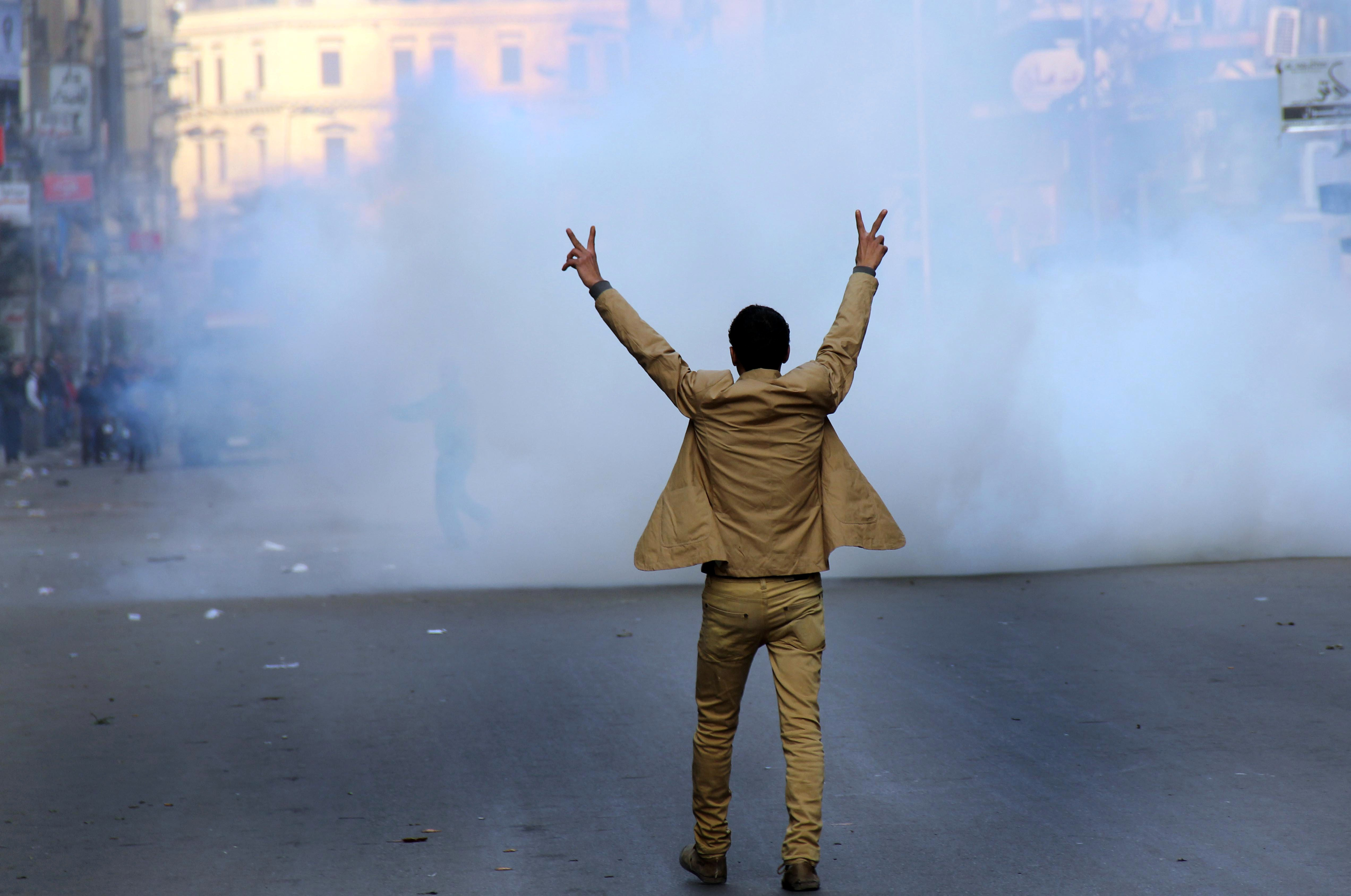 A supporter of the Egyptian government flashes the sign for victory during clashes with Muslim Brotherhood supporters (background) in Cairo on January 25, 2014. Deadly clashes erupted in Egypt Saturday as rival demonstrations were held on the anniversary of the 2011 revolt that toppled Hosni Mubarak, underscoring the country's violent polarisation three years after the Arab Spring.  (AFP PHOTO/AHMED TARANH)