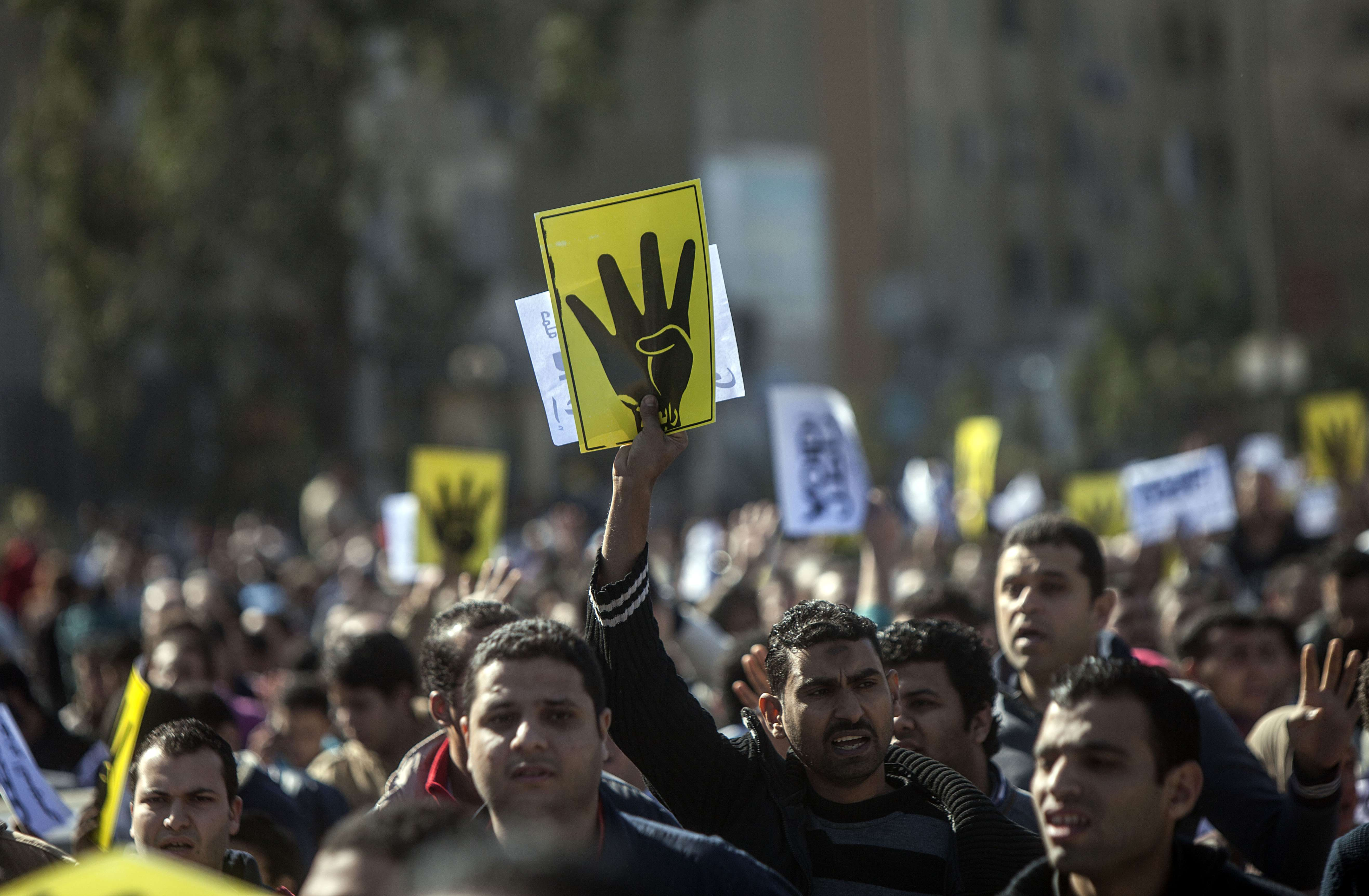 """Supporters of the Muslim Brotherhood chant slogans and raise four fingers, the symbol known as """"Rabaa"""", which means four in Arabic, remembering those killed in the crackdown on the Rabaa al-Adawiya protest camp in Cairo last year, during a demonstration in Cairo on January 24, 2014. A suicide bomber struck Cairo police headquarters on Friday, the first of three bombings in the Egyptian capital that killed five people ahead of the anniversary of the 2011 uprising.  (AFP PHOTO/MAHMOUD KHALED)"""