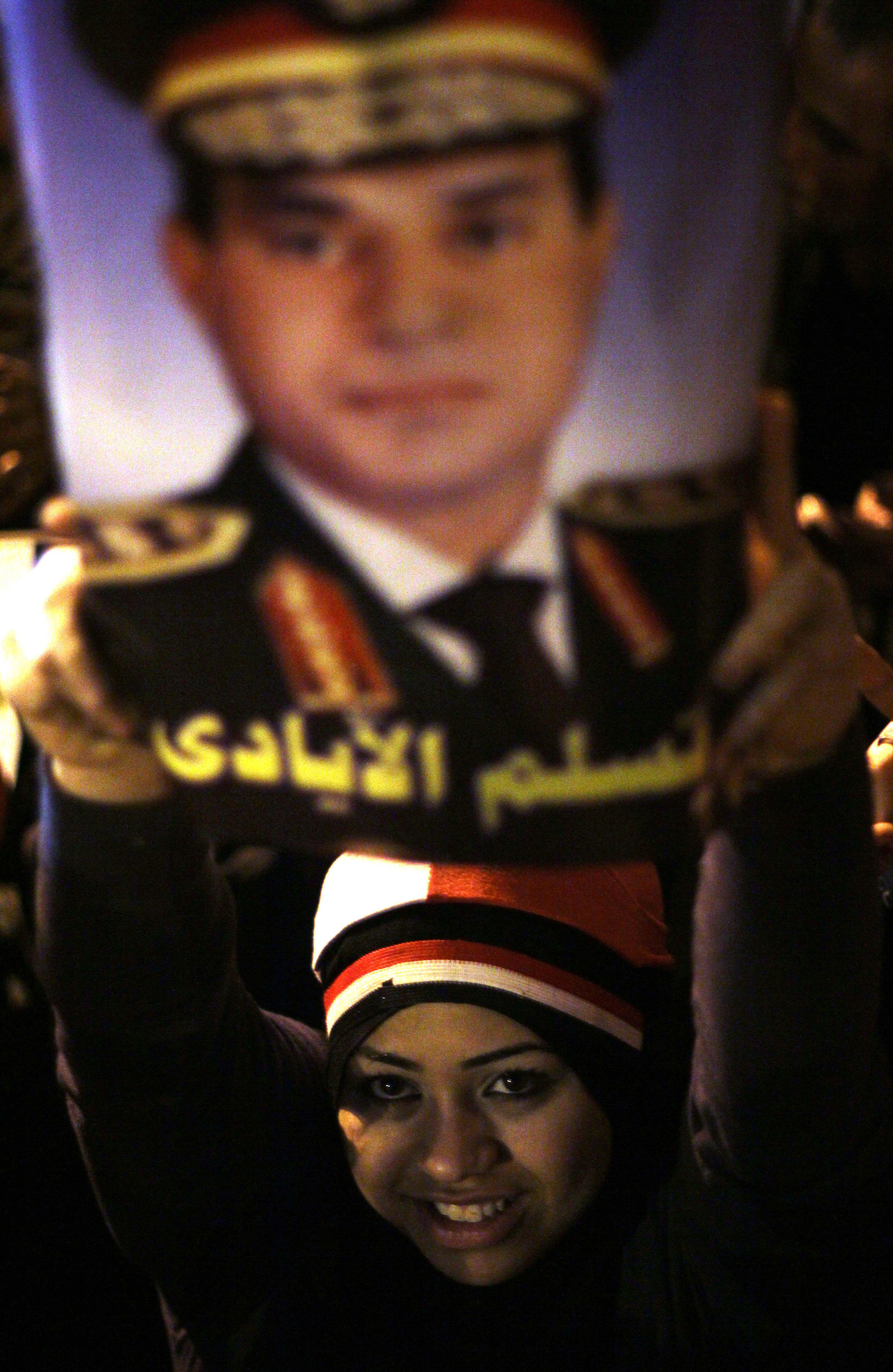 An Egyptian supporter of Egyptian Defence Minister army chief Abdel Fattah al-Sisi holds up his portrait during a gathering in General Abdel Monim Riyad square in downtown Cairo on January 25, 2014, as thousands of Egyptians rallied in the capital's Tahrir Square calling for another military man to become their leader. A spate of deadly bombings put Egyptian police on edge as supporters and opponents of the military-installed government take part in rival rallies for the anniversary of the 2011 Arab Spring uprising.  (AFP PHOTO/AHMED TARANH)