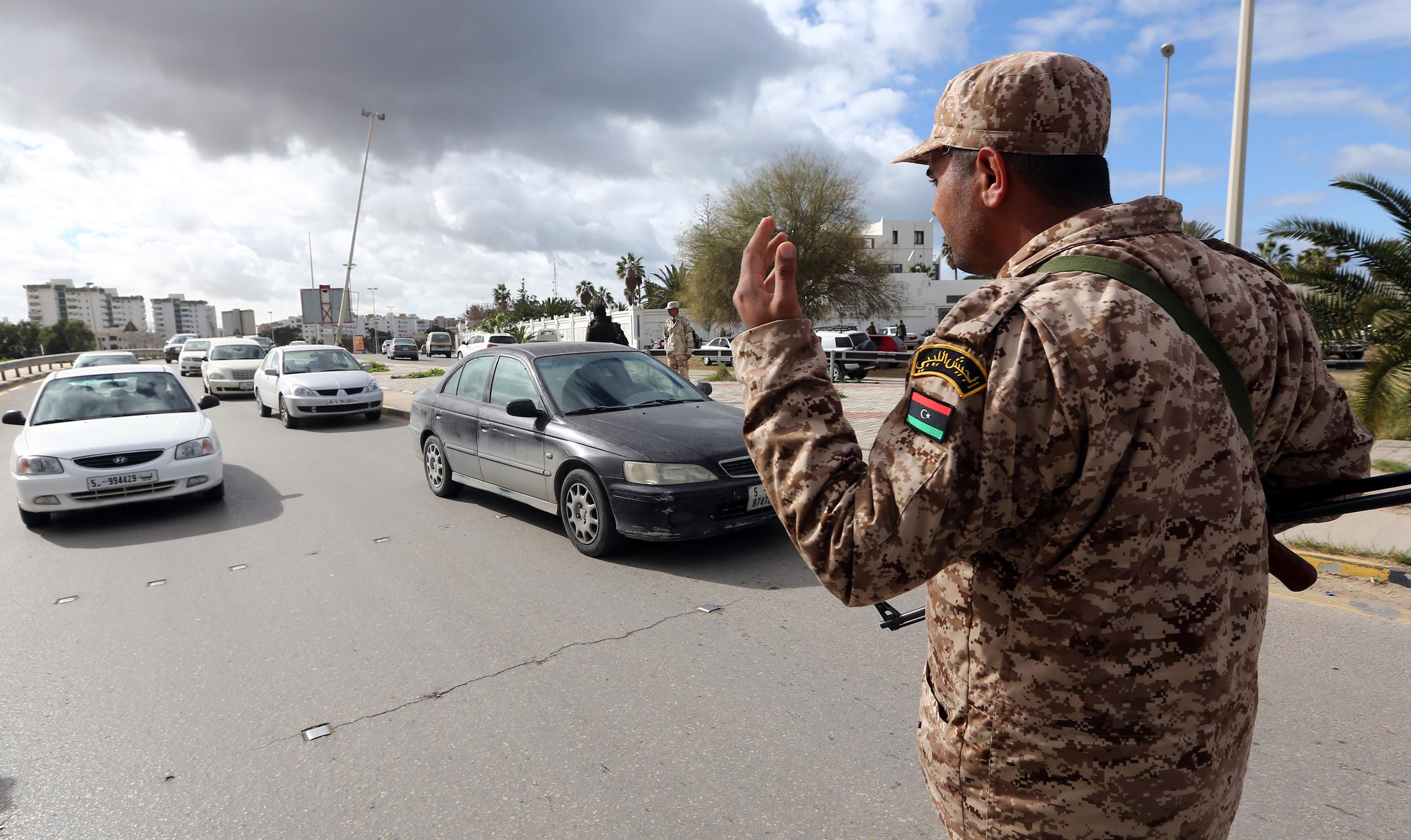 A soldier from the Libyan army mans a checkpoint in the capital Tripoli on January 26, 2014. Egypt's ambassador and his staff have left Libya for security reasons after the kidnapping of five of their colleagues, the foreign ministry said. The evacuation had been decided on security grounds, he said, as Libyan authorities worked to secure the release of the abducted diplomats.  (AFP PHOTO/MAHMUD TURKIA)