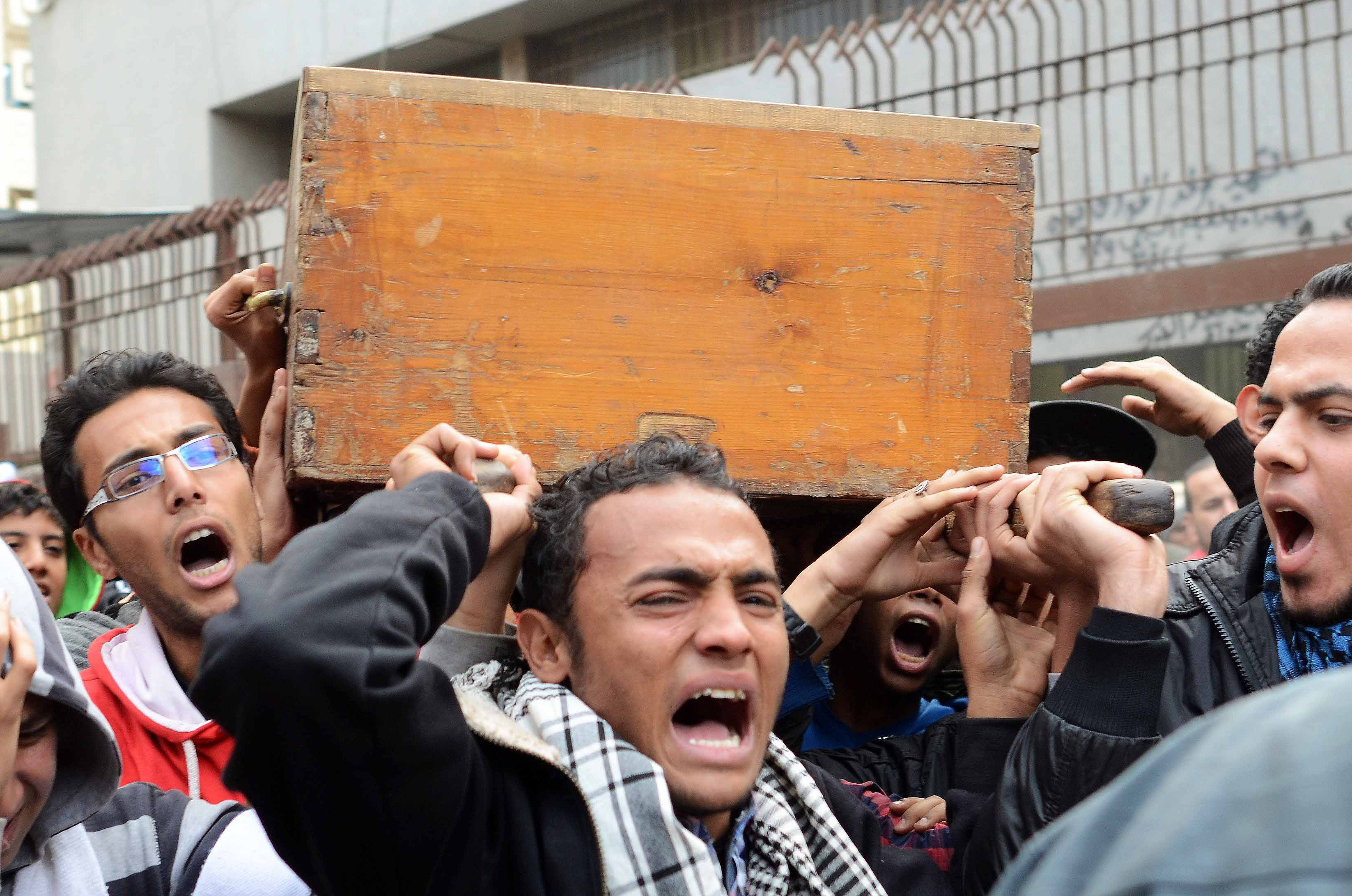 The coffin of one of the victims of clashes between supporters and opponents of Egypt's military is carried outside the Zinhom Morgue on January 26, 2014, outside Cairo, Egypt.  (AFP PHOTO MOHAMED EL-SHAHED)