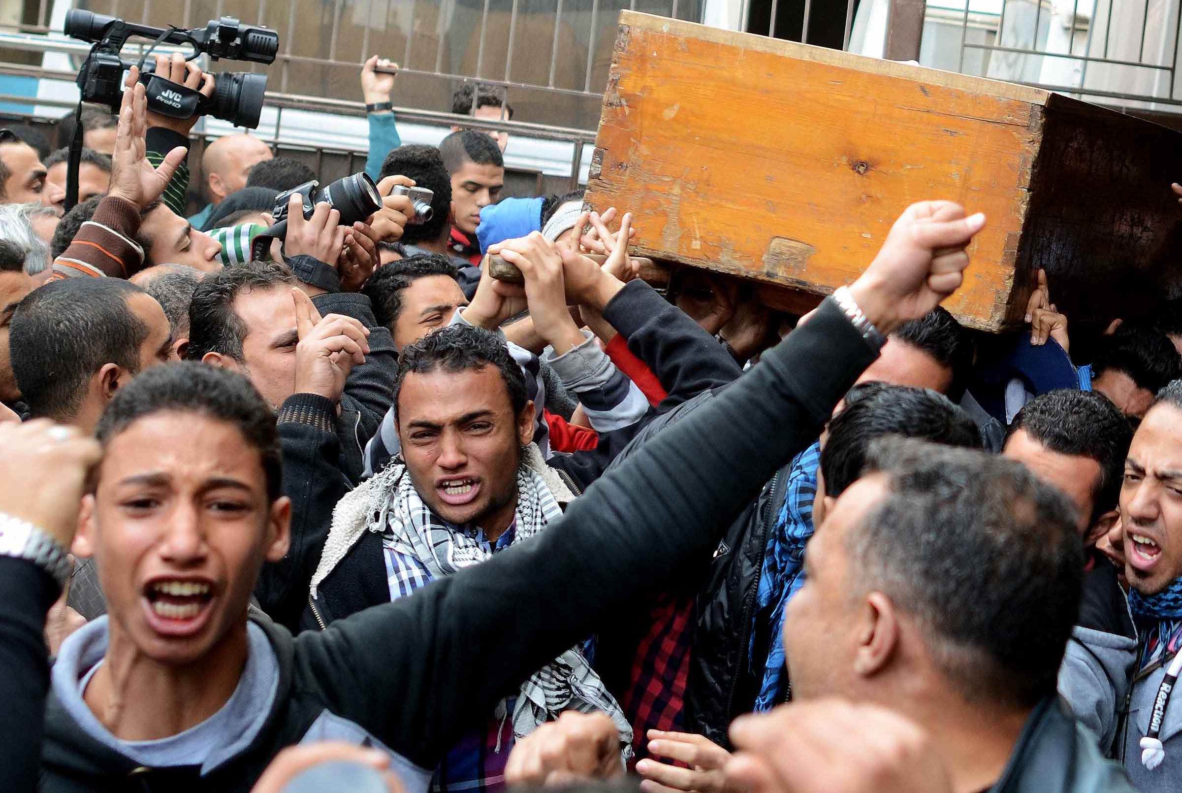 People mourn as they carry the coffin of one of the victims of clashes between supporters and opponents of Egypt's military, on January 26, 2014 outside the Zinhom Morgue, outside Cairo, Egypt. Nearly 50 people died in weekend clashes between supporters and opponents of Egypt's military, as media outlets on January 25, 2014 hailed rallies urging the army chief to run for the presidency.     (AFP PHOTO MOHAMED EL-SHAHED)