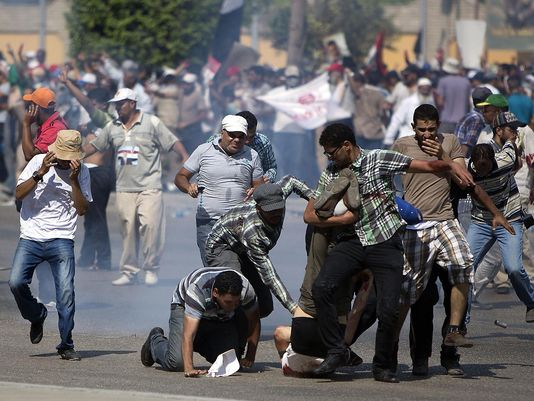 Supporters of ousted Egyptian president Mohammed Morsi rush to help a wounded man after a gunbattle erupted outside the Cairo headquarters of the Republican Guard on Friday. (Photo: Mahmud Hamsud, AFP/Getty Images)