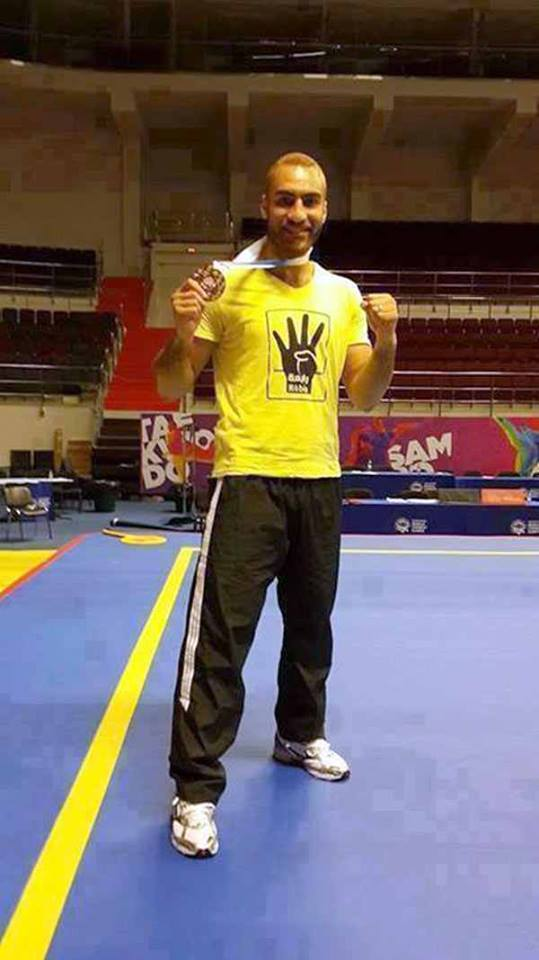 Kung Fu player Mohamed Youssef who claimed the gold medal in the Sports Accord Combat Games competition in St. Petersburg Russia on Sunday, during the medal ceremony raised the four-finger Rabaa sign and wore a t-shirt displaying the same symbol, which symbolises support for the Rabaa-Al Adaweya sit-in in support of former President Mohamed Morsi. (Photo from FJP)