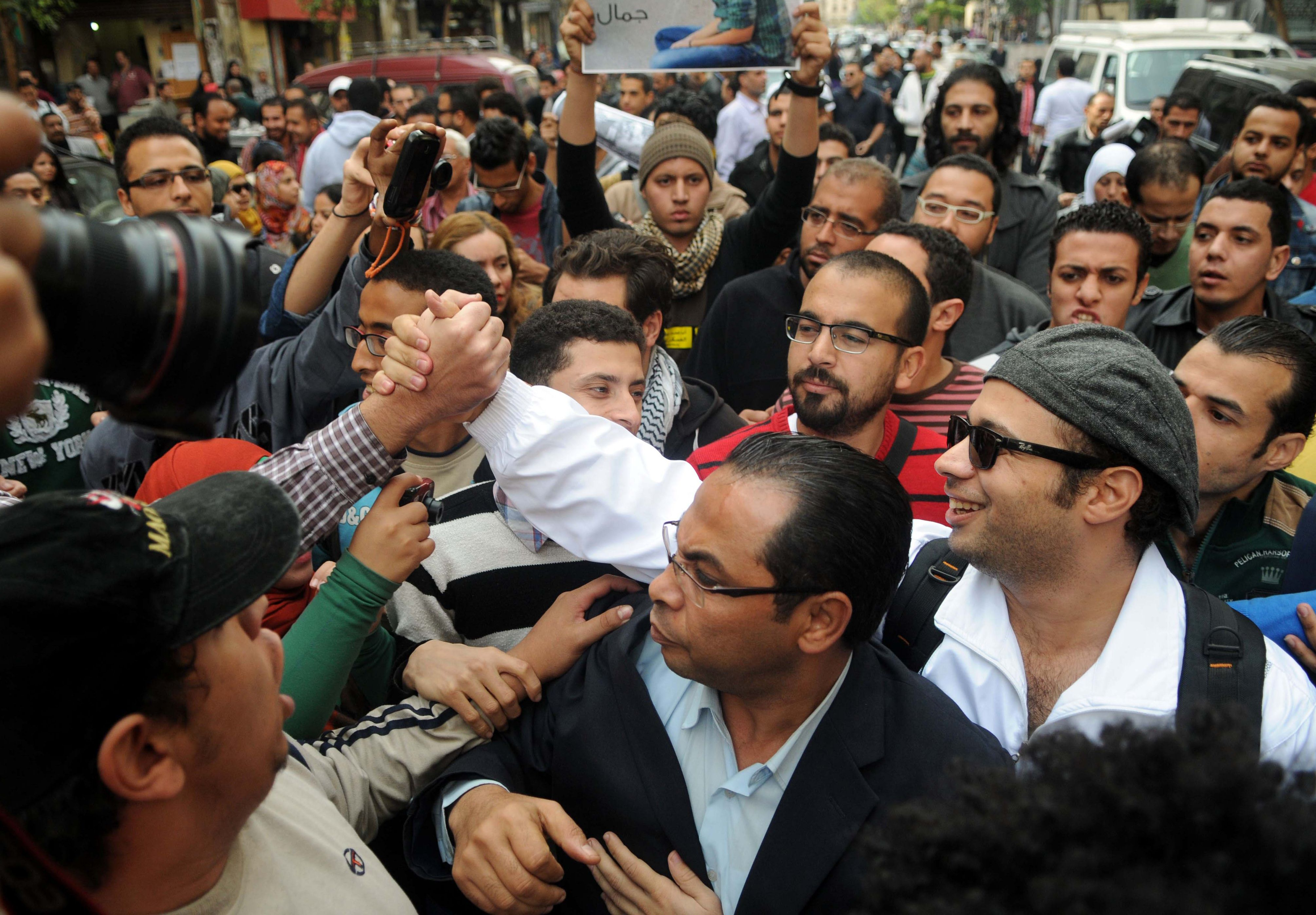 Ahmed Maher (R), co-founder of the 6 April youth movement that spearheaded Mubarak's ousting, is greeted by supporters as he comes to hand himself in to prosecutors on November 30, 2013 in the Egyptian capital, Cairo after an arrest warrant was issued on charges of inciting demonstrations against the new protest law. Ahmed Maher was surrounded upon his arrival by dozens of supporters who chanted slogans demanding the release of other detained activists.  (AFP PHOTO/ STR)