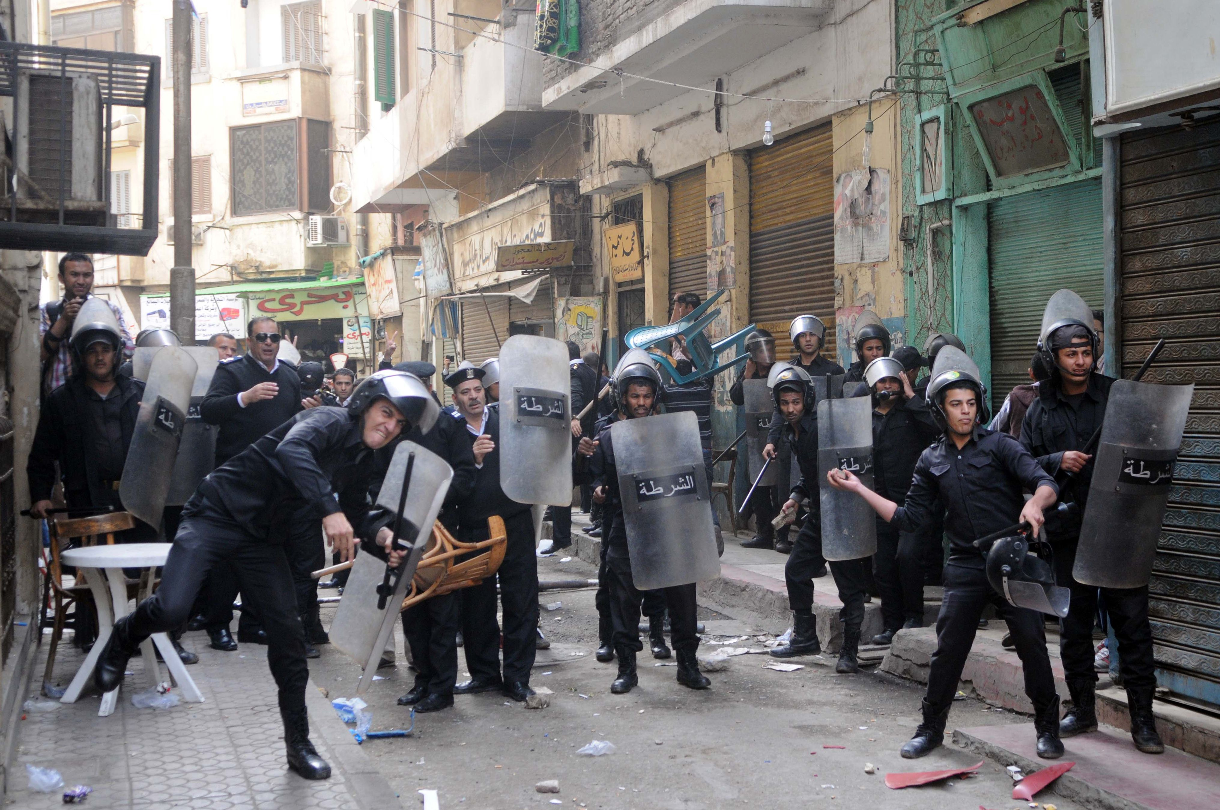 Egyptian riot policemen throw stones during clashes with protesters who gathered in support of a prominent secular activist who turned himself after being ordered detained for holding a demonstration against a new protest law, on November 30, 2013 in the Egyptian capital, Cairo. Ahmed Maher, founder of the April 6 movement, one of the main groups that spearheaded the 2011 revolt against long-time ruler Hosni Mubarak, arrived at a Cairo court surrounded by dozens of supporters who chanted slogans demanding the release of other detained activists.     (AFP PHOTO STR)
