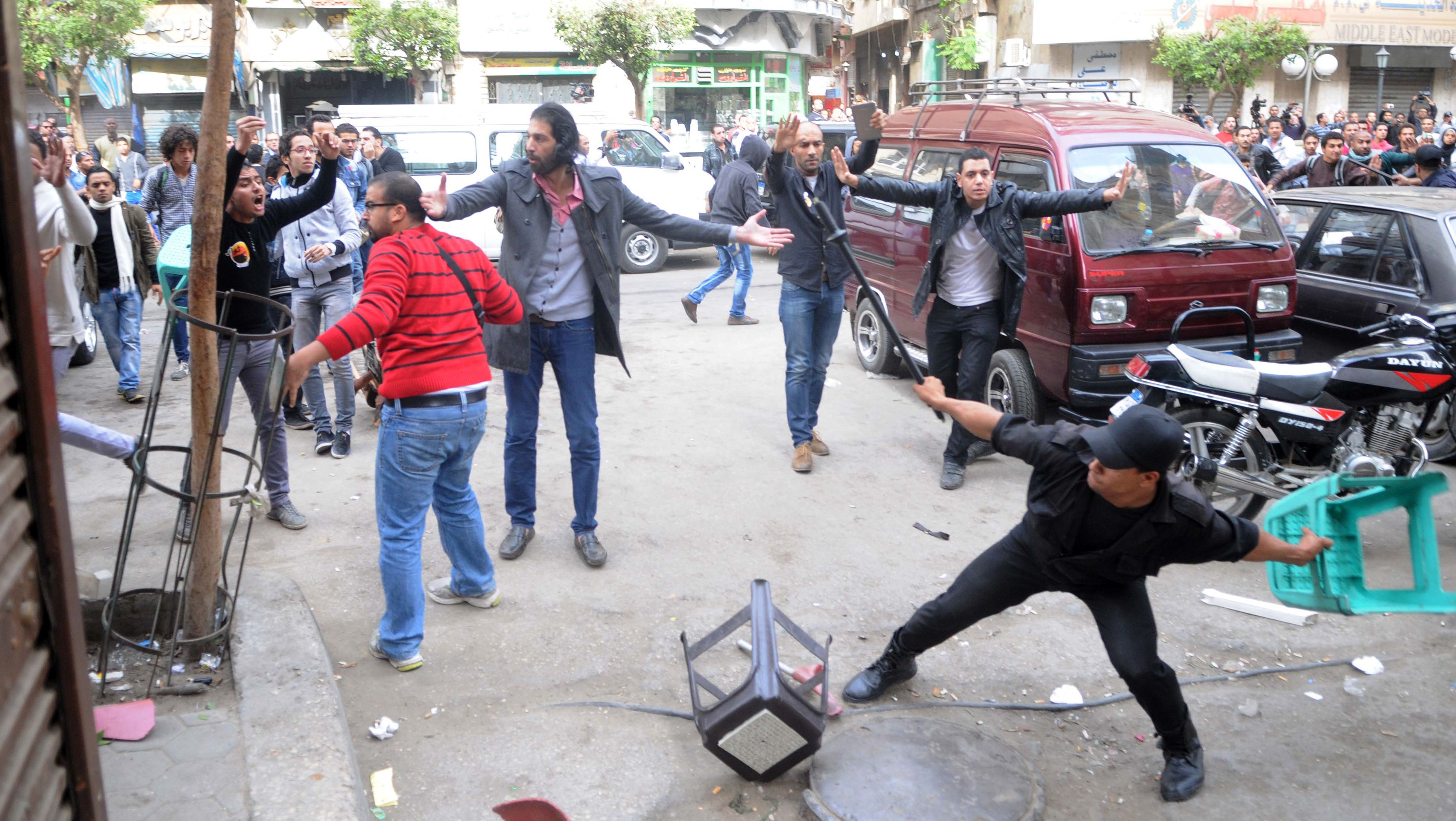 A member of Egyptian security forces throws a plastic stool during clashes with protesters who gathered in support of a prominent secular activist who turned himself after being ordered detained for holding a demonstration against a new protest law, on November 30, 2013 in the Egyptian capital, Cairo. Ahmed Maher, founder of the April 6 movement, one of the main groups that spearheaded the 2011 revolt against long-time ruler Hosni Mubarak, arrived at a Cairo court surrounded by dozens of supporters who chanted slogans demanding the release of other detained activists.    (AFP PHOTO STR)
