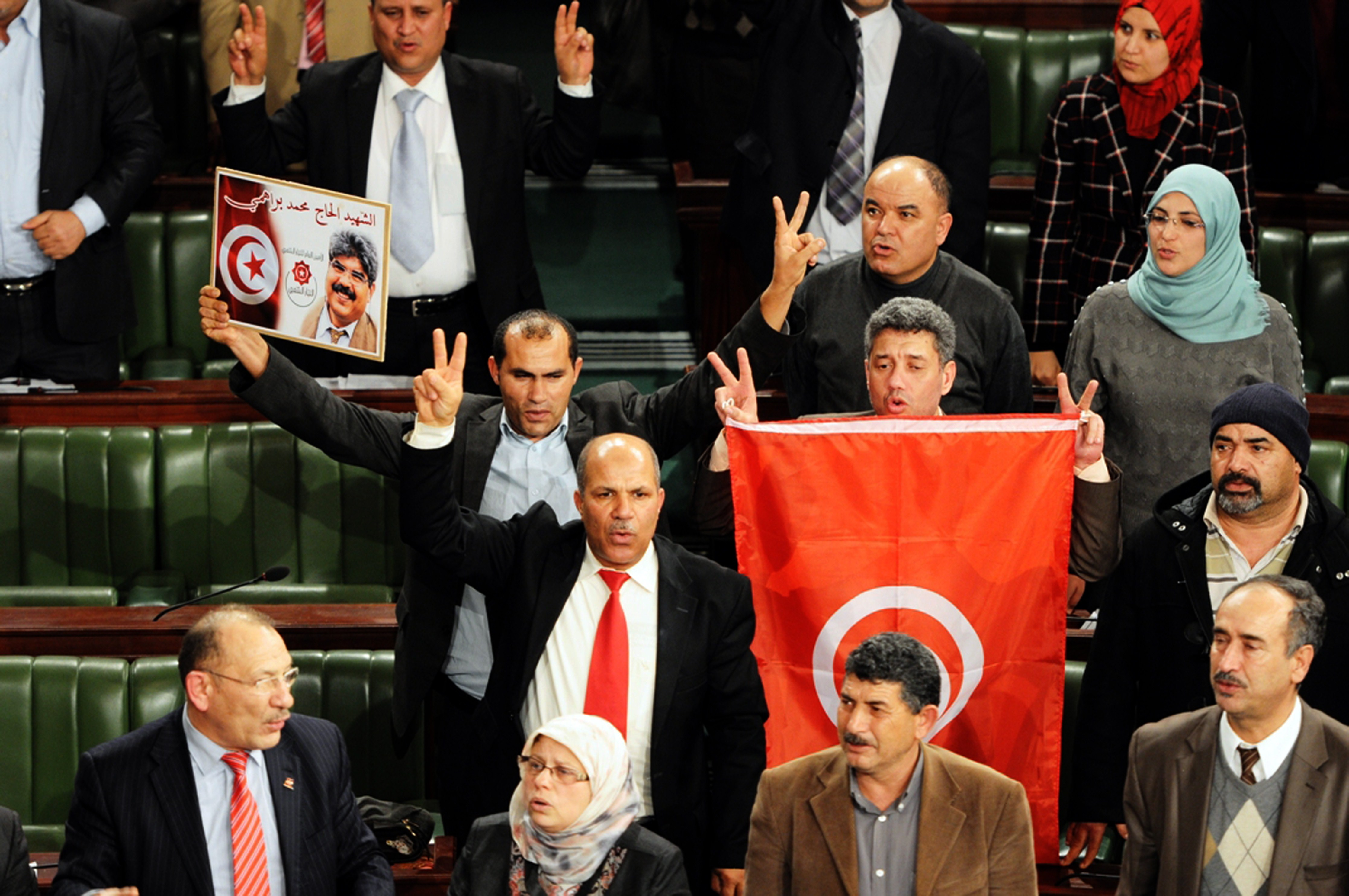 Members of the Tunisian National Constituent Assembly (NCA) jubilate after the adoption of a new constitution on January 26, 2014, in Tunis. Tunisia's constituent assembly late on Sunday adopted a new constitution, more than three years after the revolution which began the Arab Spring.  The assembly approved the constitution by an overwhelming majority, with 200 votes in favour, 12 against and four abstentions a live television broadcast showed.   (AFP PHOTO / STR)