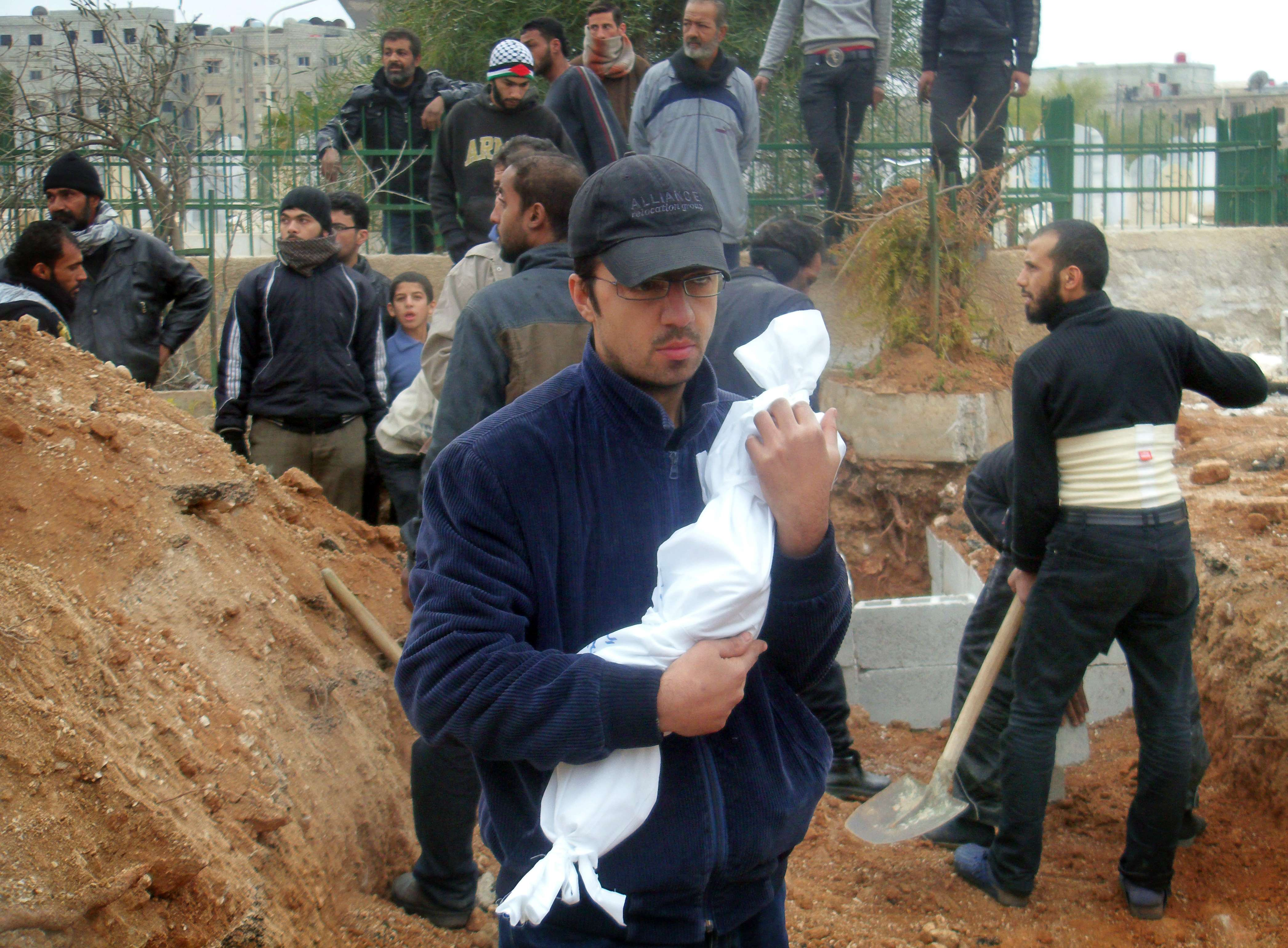 A man holds the corpse of one-year old baby Adbul Jalil Mohamed Hamis wrapped in shrouds, who reportedly died of hunger in the besieged Yarmuk Palestinian refugee camp in southern Damascus during a funeral ceremony on January 27, 2014. The previous week the Syrian Observatory for Human Rights reported that 63 people, including women and children, died due to starvation and a lack of medical supplies in the camp of Yarmuk.  (AFP PHOTO / STR / LENS OF A YOUNG DIMASHQI)