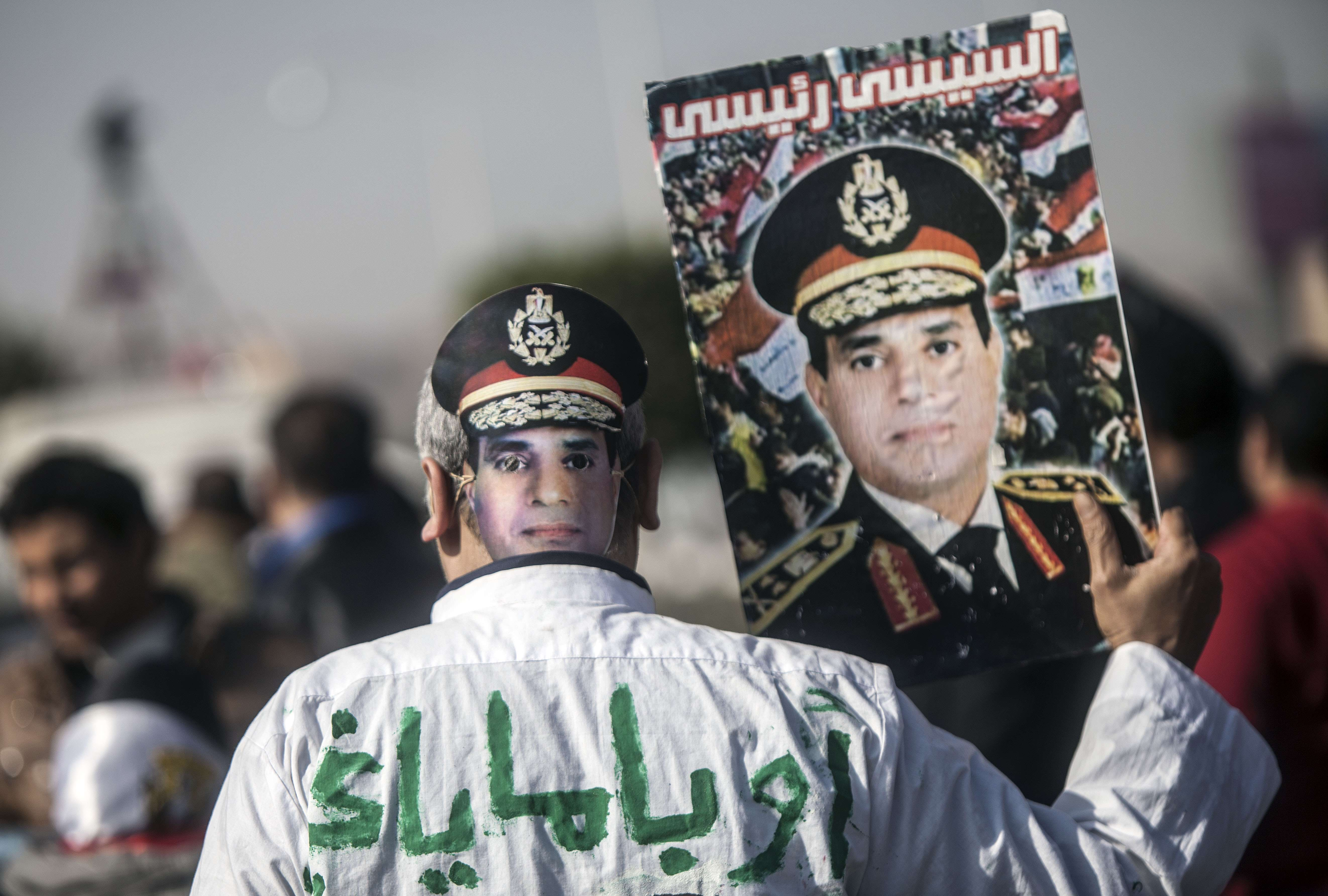 A supporter of Egypt's army chief Field Marshal Abdel Fattah al-Sisi, who is to run for the presidency in the upcoming elections, wears a mask and holds a portrait bearing the image of the military commander as he demonstrates outside the Police Academy in Cairo where a new hearing in the trial of deposed president Mohamed Morsi opened on January 28, 2014. Morsi went on trial on charges of breaking out of prison during the 2011 uprising against veteran strongman Hosni Mubarak.  (AFP PHOTO / MAHMUD KHALED)