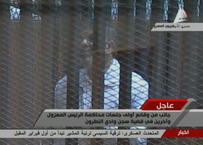 "An image grab taken from Egyptian state television shows deposed Egyptian president Mohamed Morsi in the accused cage in a makeshift courtroom inside a police academy on the outskirts of Cairo on January 28, 2014  during his trial on charges of breaking out of prison during the 2011 uprising against veteran strongman Hosni Mubarak. Morsi is being tried with 130 others, including members of his banned Muslim Brotherhood, the Islamist Palestinian movement Hamas and Lebanon's Shiite militant group Hezbollah.   AFP PHOTO / EGYPTIAN TV == RESTRICTED TO EDITORIAL USE - MANDATORY CREDIT ""AFP PHOTO / EGYPTIAN TV"" - NO MARKETING NO ADVERTISING CAMPAIGNS - DISTRIBUTED AS A SERVICE TO CLIENTS ==="