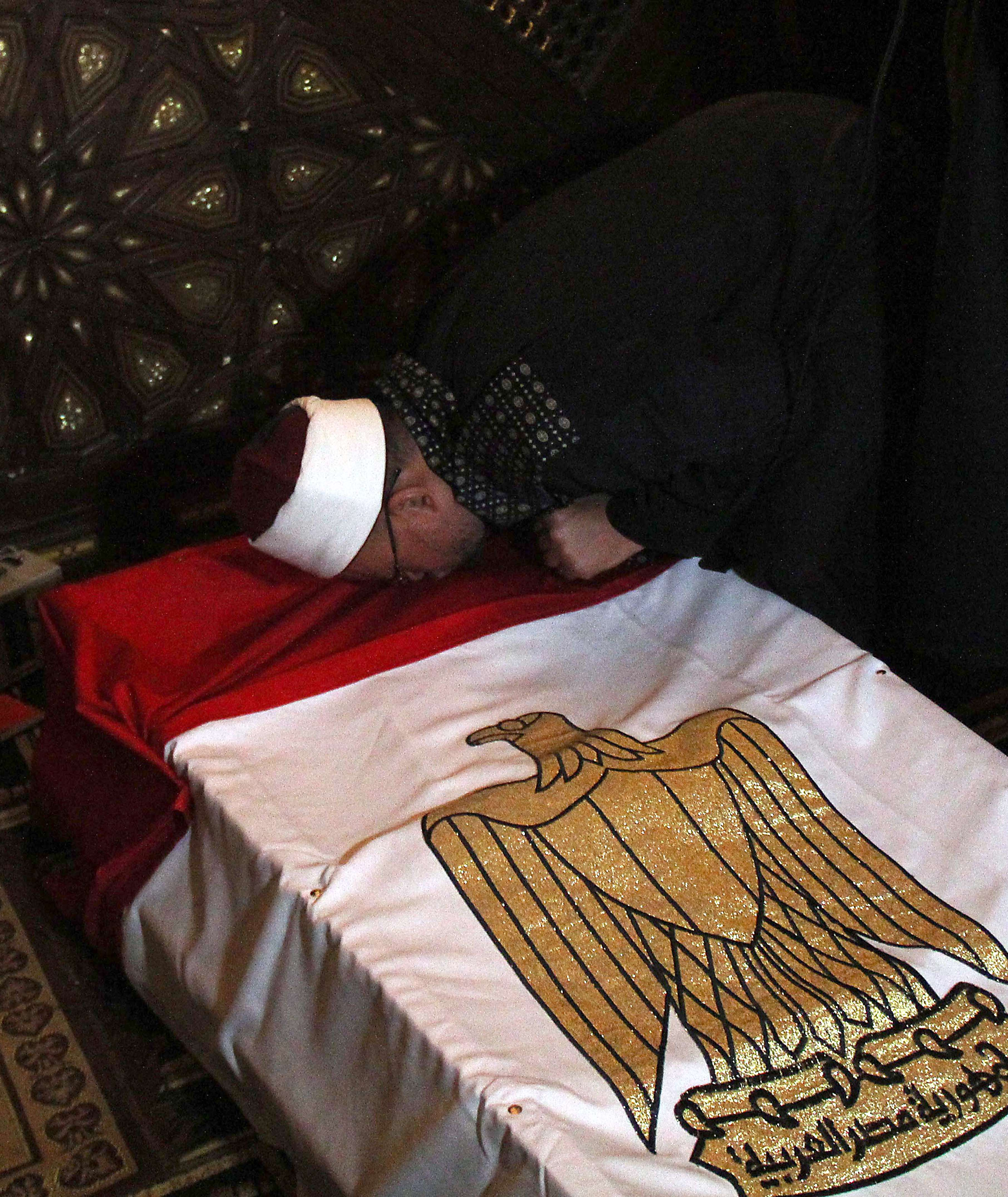 """An Egyptian Muslim cleric kisses the coffin of the General Mohamed Saeed during his funeral, on January 28, 2014 in Cairo. Saeed, who was the head of interior minister Mohamed Ibrahim's """"technical department, was killed while leaving his home in a west Cairo neighbourhood when gunmen on a motorbike opened fire at him, hitting him in the head and the chest, security officials said.    (AFP PHOTO/AHMED TARANA)"""