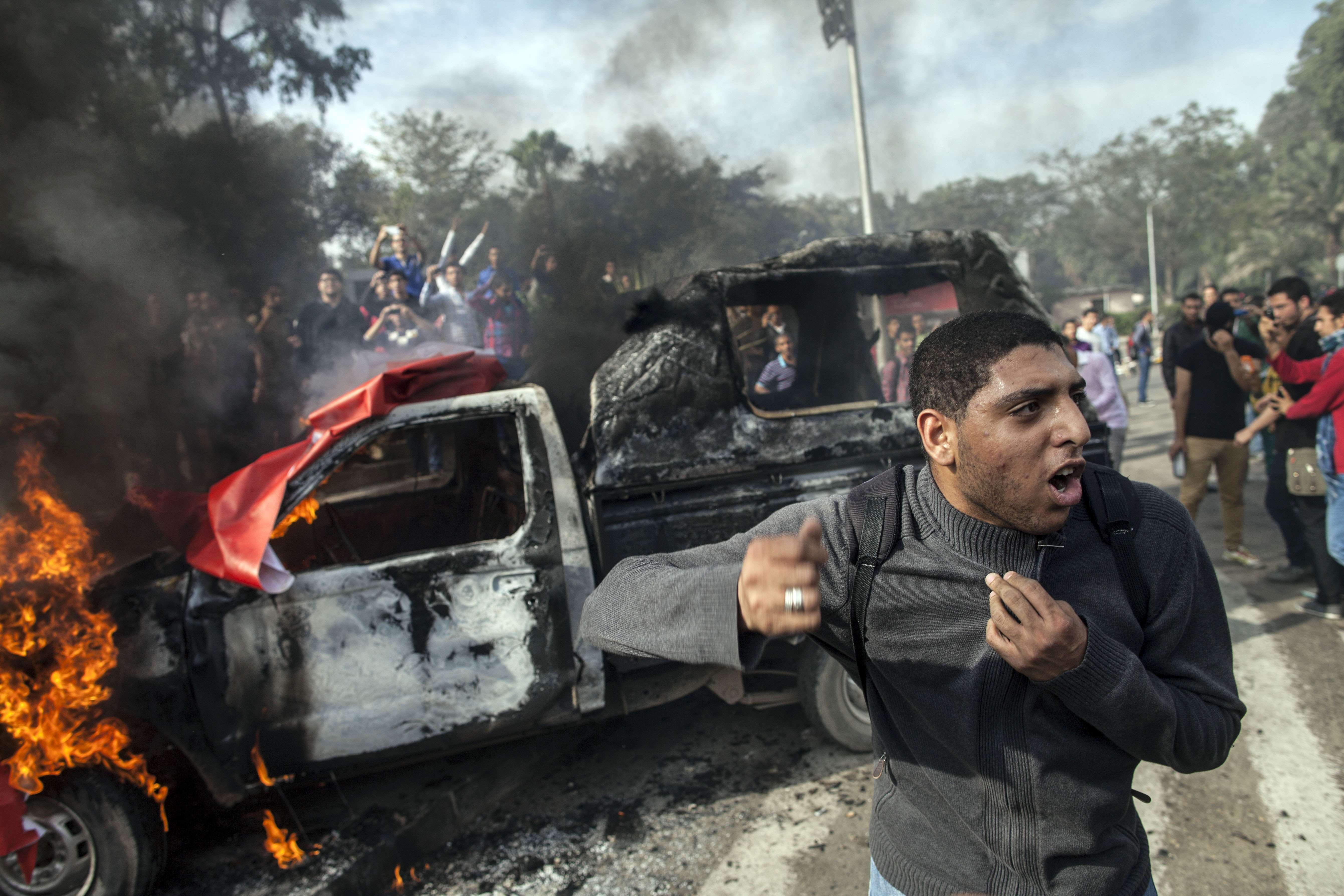 An Egyptian student at Cairo's University stands in front of a police vehicle burning on December 1, 2013 during a demonstration in support of a felow engineering student who was killed the previous week during clashes with Egyptian security forces in an Islamist demonstration. ( AFP PHOTO/MAHMOUD KHALED)