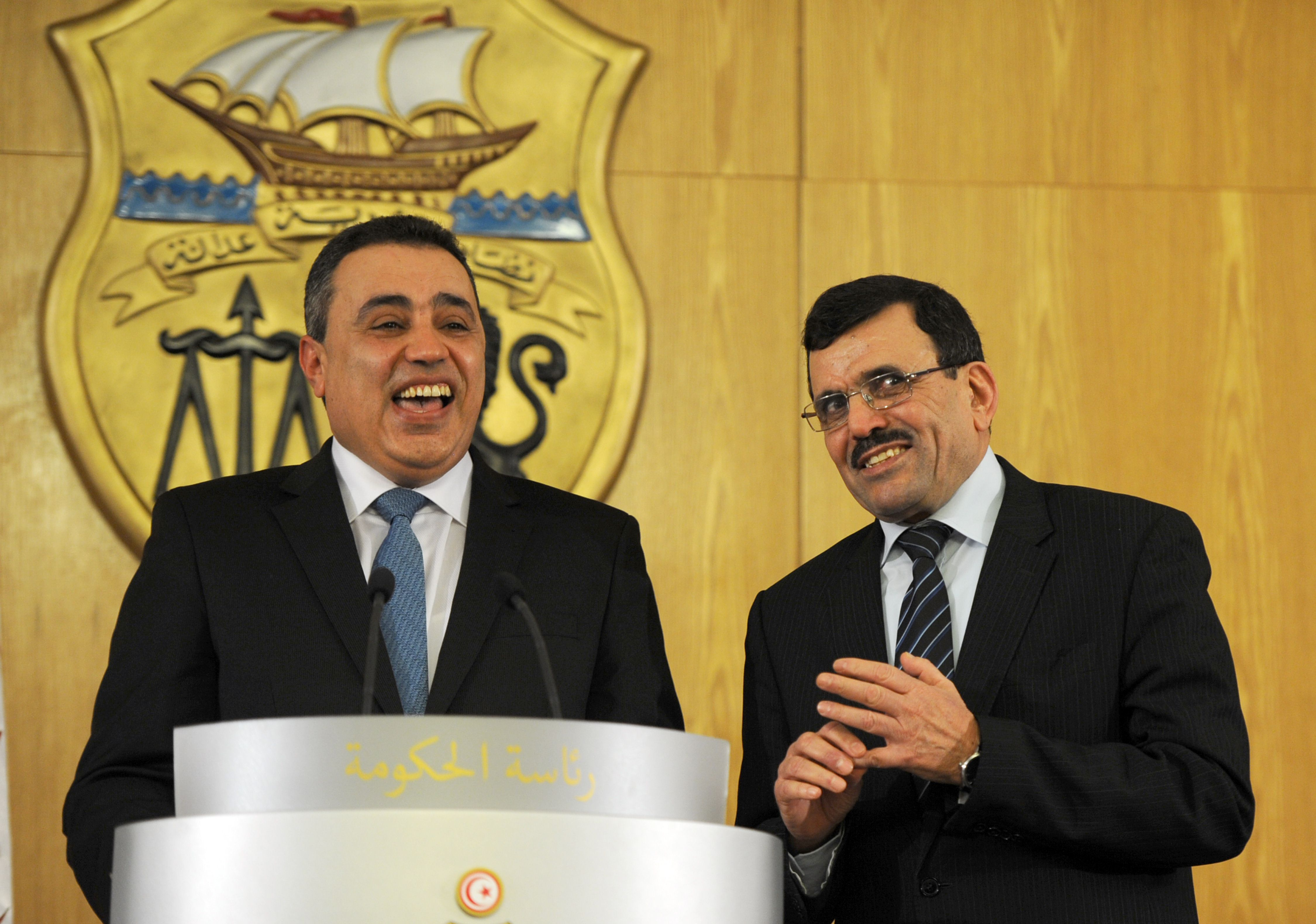 Tunisia's new Prime minister Mehdi Jomaa (L) stands at the podium next to his predecessor Ali Laarayedh during a handover ceremony in Tunis on January 29, 2014. Tunisia's parliament approved a technocratic caretaker government tasked with leading the country out of a bruising political crisis and into fresh elections.   (AFP PHOTO/FETHI BELAID)