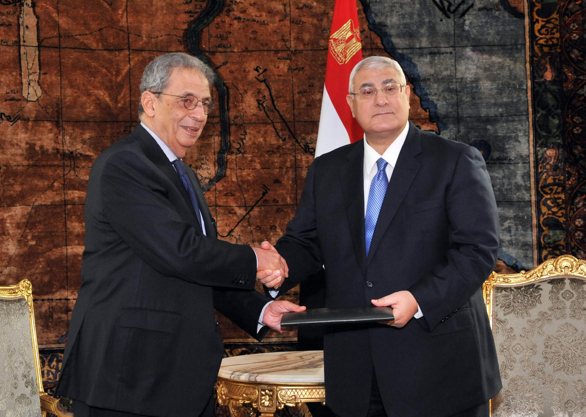 "A handout picture released by Egyptian presidency shows Egypt's interim president Adly Mansour (R) receiving the draft constitution from Amr Mussa, chairman of the Egyptian Constitutional panel at the presidential palace in Cairo on December 3, 2013. The text of a new constitution that would consolidate the power of the army was handed over to Egypt's interim president, giving him a month to call a referendum. AFP PHOTO / HO / EGYPTIAN PRESIDENCY === RESTRICTED TO EDITORIAL USE - MANDATORY CREDIT ""AFP PHOTO/HO/EGYPTIAN PRESIDENCY"" - NO MARKETING NO ADVERTISING CAMPAIGNS - DISTRIBUTED AS A SERVICE TO CLIENTS ==="
