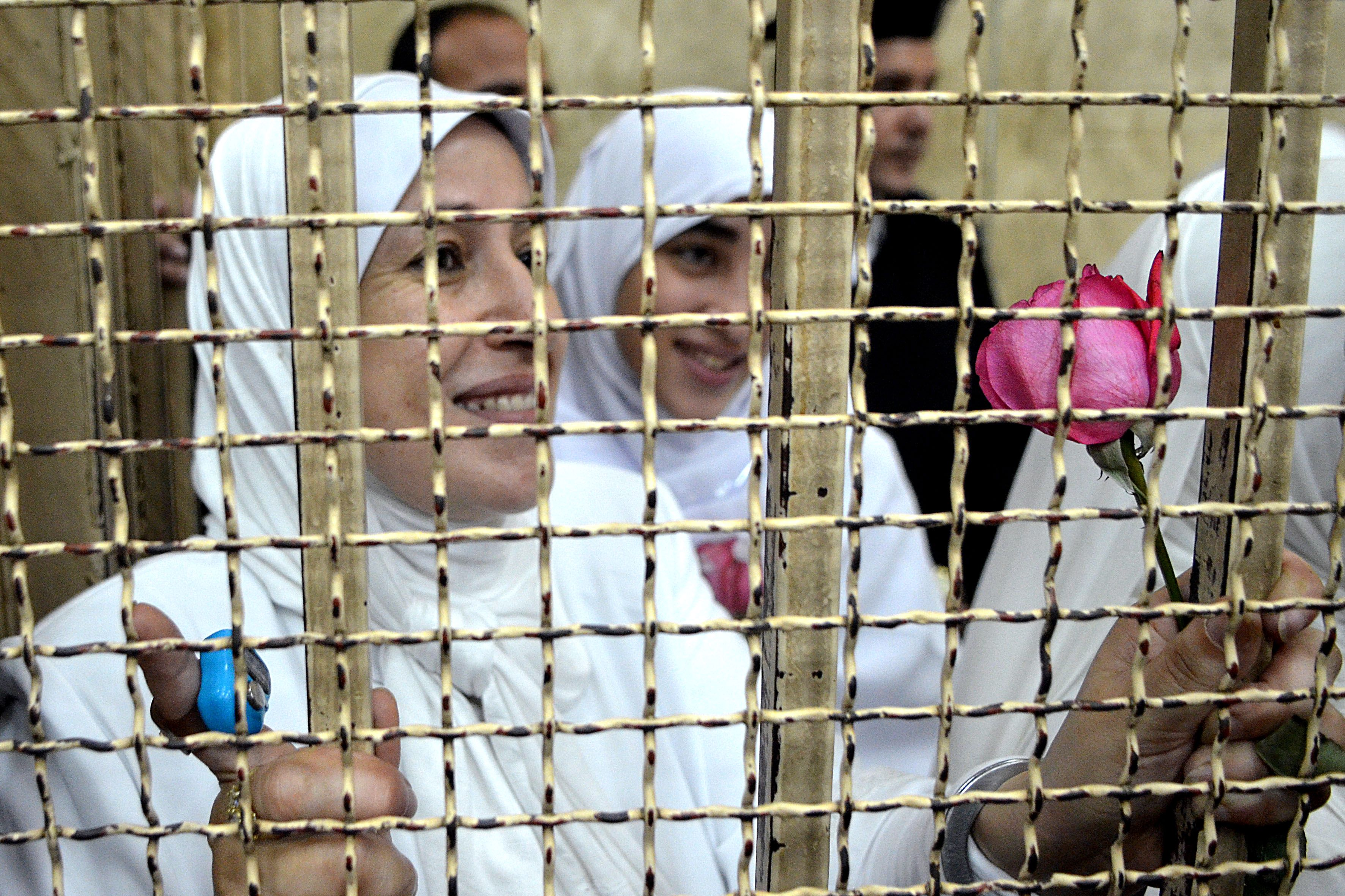 Egyptian women members of the Muslim Brotherhood hold roses as they stand in the defendants' cage dressed in prison issue white during their trial in at the court in the Egyptian Mediterranean city of Alexandria on December 7, 2013. Egyptian judges began hearing appeals of 21 women and girls handed heavy jail terms over an Islamist protest, in a case that sparked an outcry. The 14 adult women were handed 11-year jail terms and the seven minors sentenced to juvenile detention last month, shocking even supporters of the military-installed government.  (AFP PHOTO/STR)