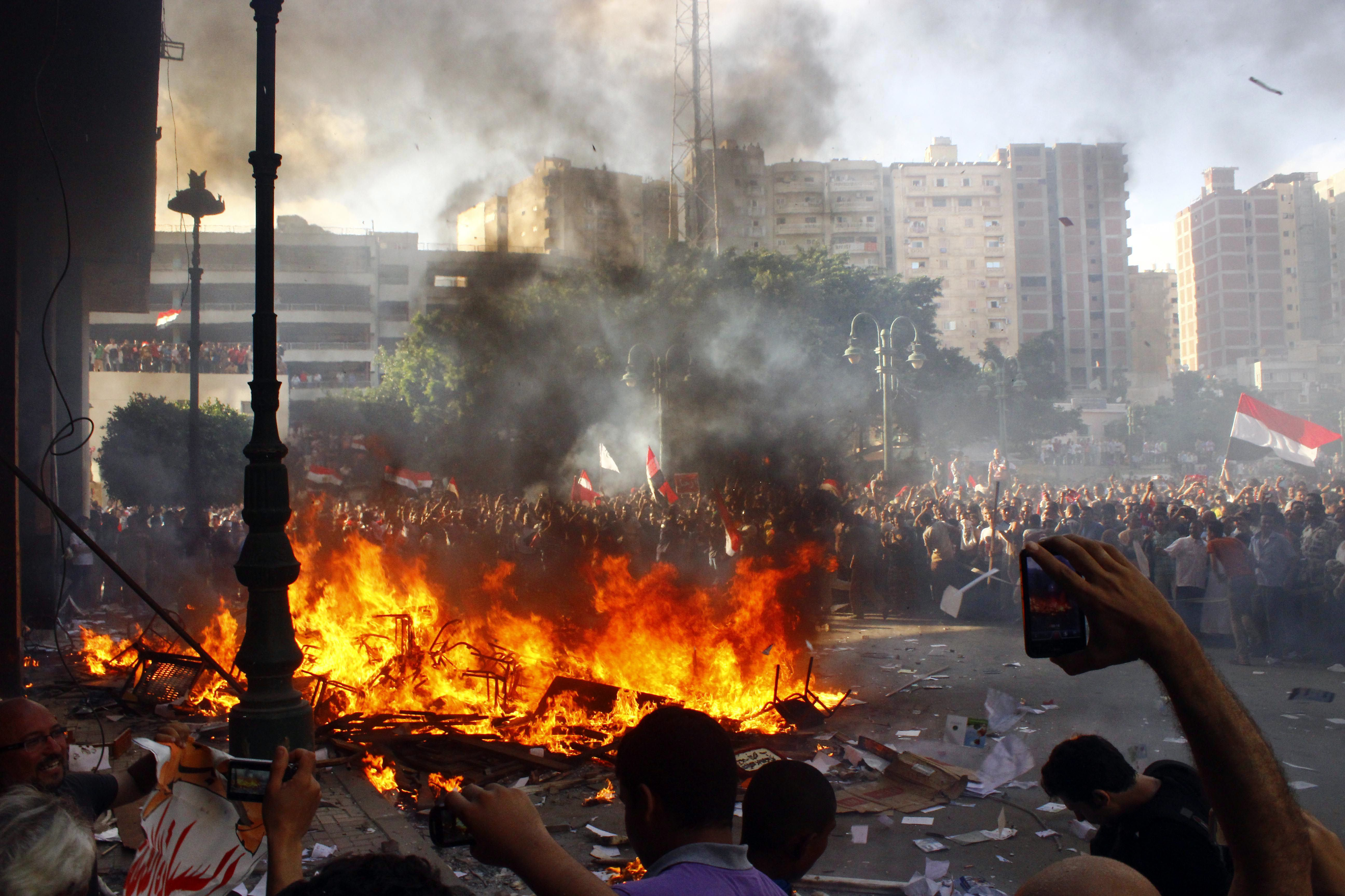Opponents of Egyptian President Mohamed Morsi burn the content of a Freedom and Justice Party office in the coastal city of Alexandria on June 28, 2013. One person was killed and more than 70 injured in Egypt's second city of Alexandria on Friday as clashes raged between supporters and opponents of Islamist President Mohamed Morsi, state media reported.  (AFP PHOTO/STR)