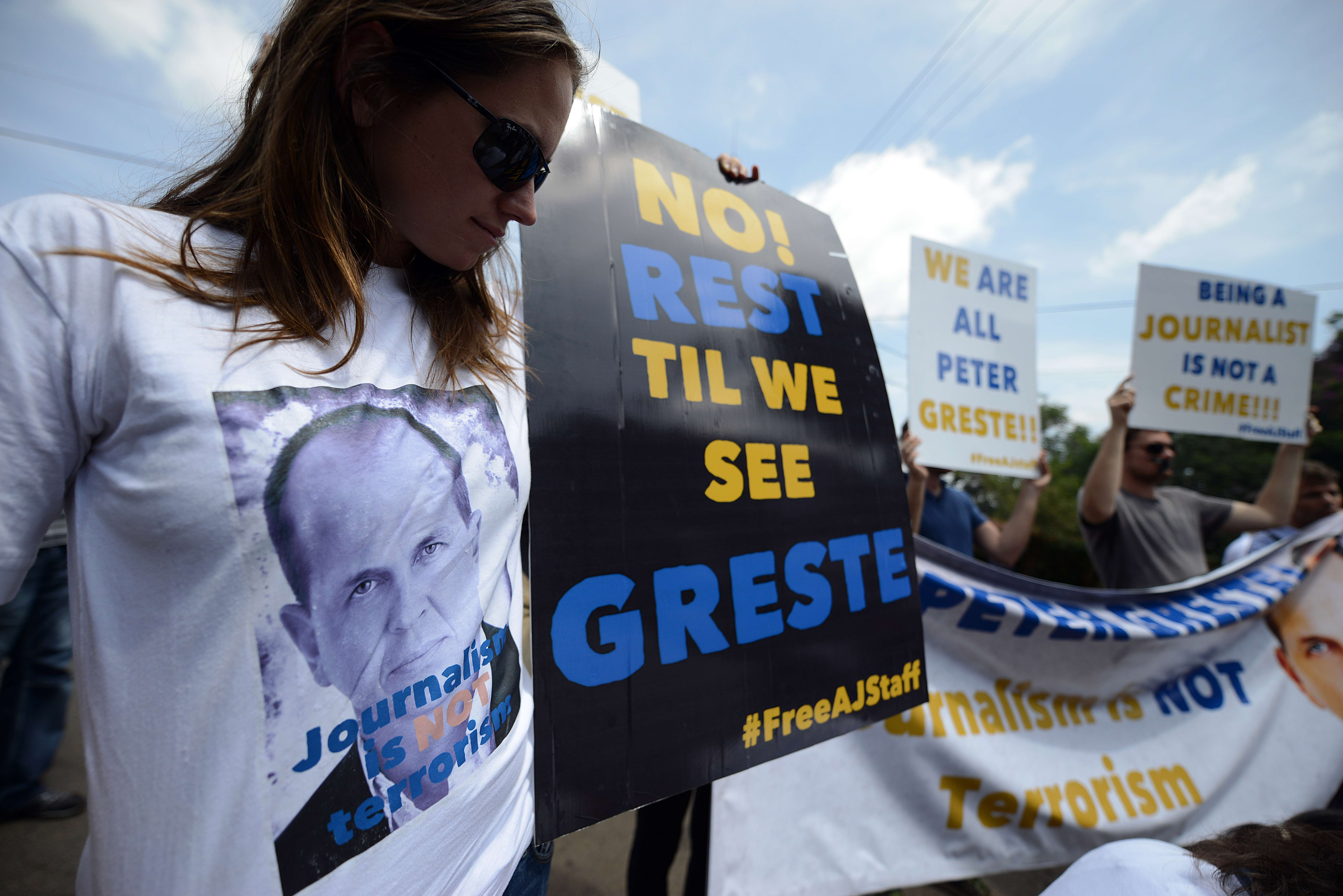 Foreign journalists march to the Egyptian Embassy in Nairobi as they wear t-shirts bearing a picture of Peter Greste, an Australian journalist who was arrested and detained in Cairo while on assignment for Qatar-based Al-Jazeera network, on December 29, 2013. Greste and two others journalists are accused of spreading lies harmful to state security and joining a terrorist organisation. (AFP PHOTO/SIMON MAINA)