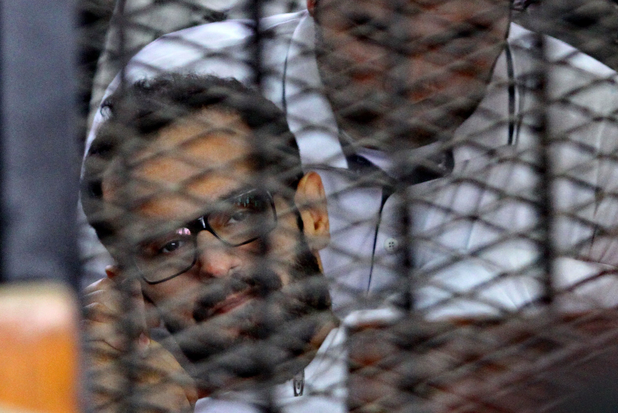 Detained American-Egyptian activist, Mohamed Sultan sits behind the bars of the accused dock during his trial on June 23, 2014 in the Egyptian capital Cairo.  (AFP PHOTO / STR)