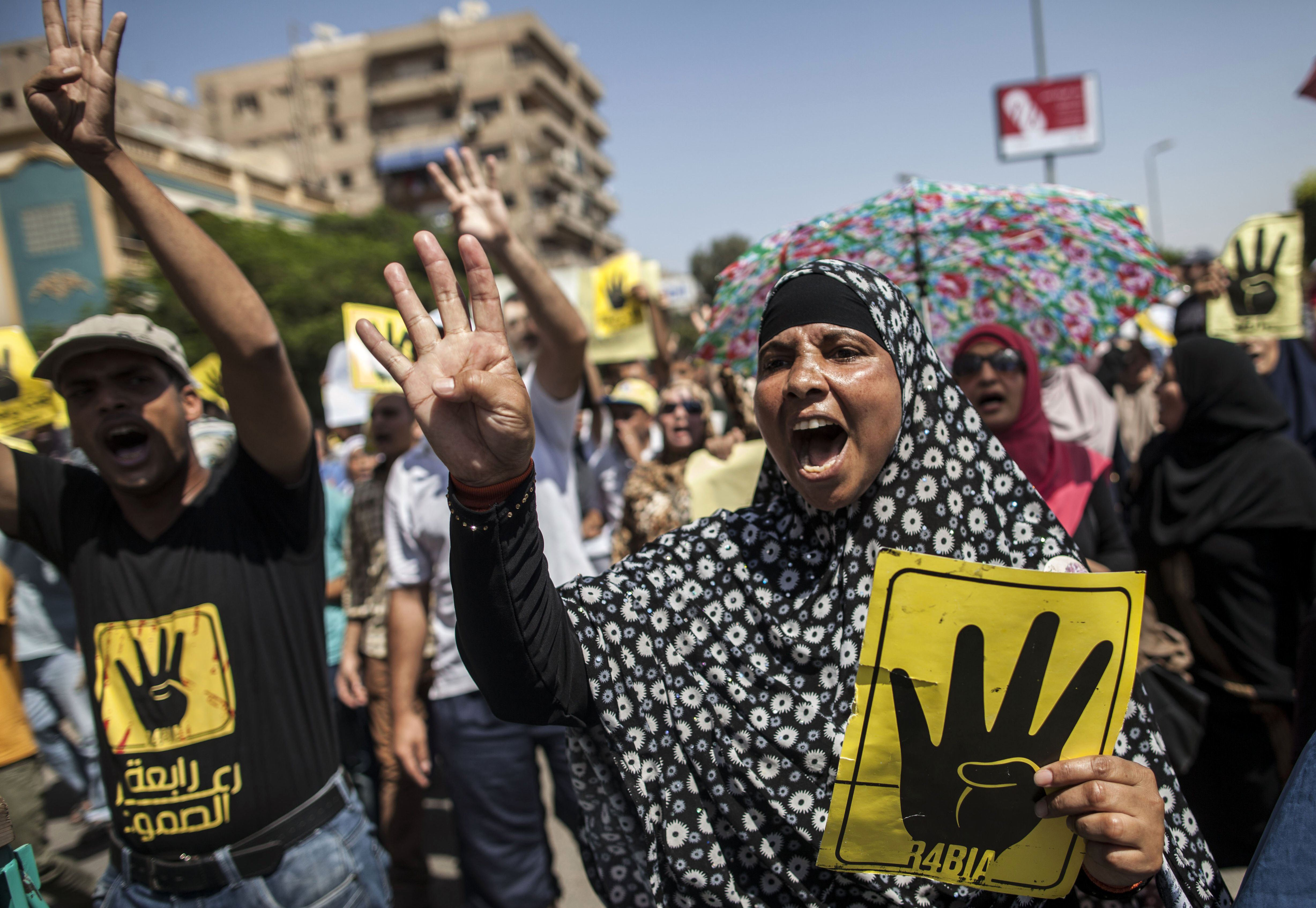 Supporters of ousted Egyptian president Mohamed Morsi raise up posters with the four finger symbol during a demonstration against the military backed government in the Egyptian capital Cairo, on 13 September 2013  (AFP/ file photo)