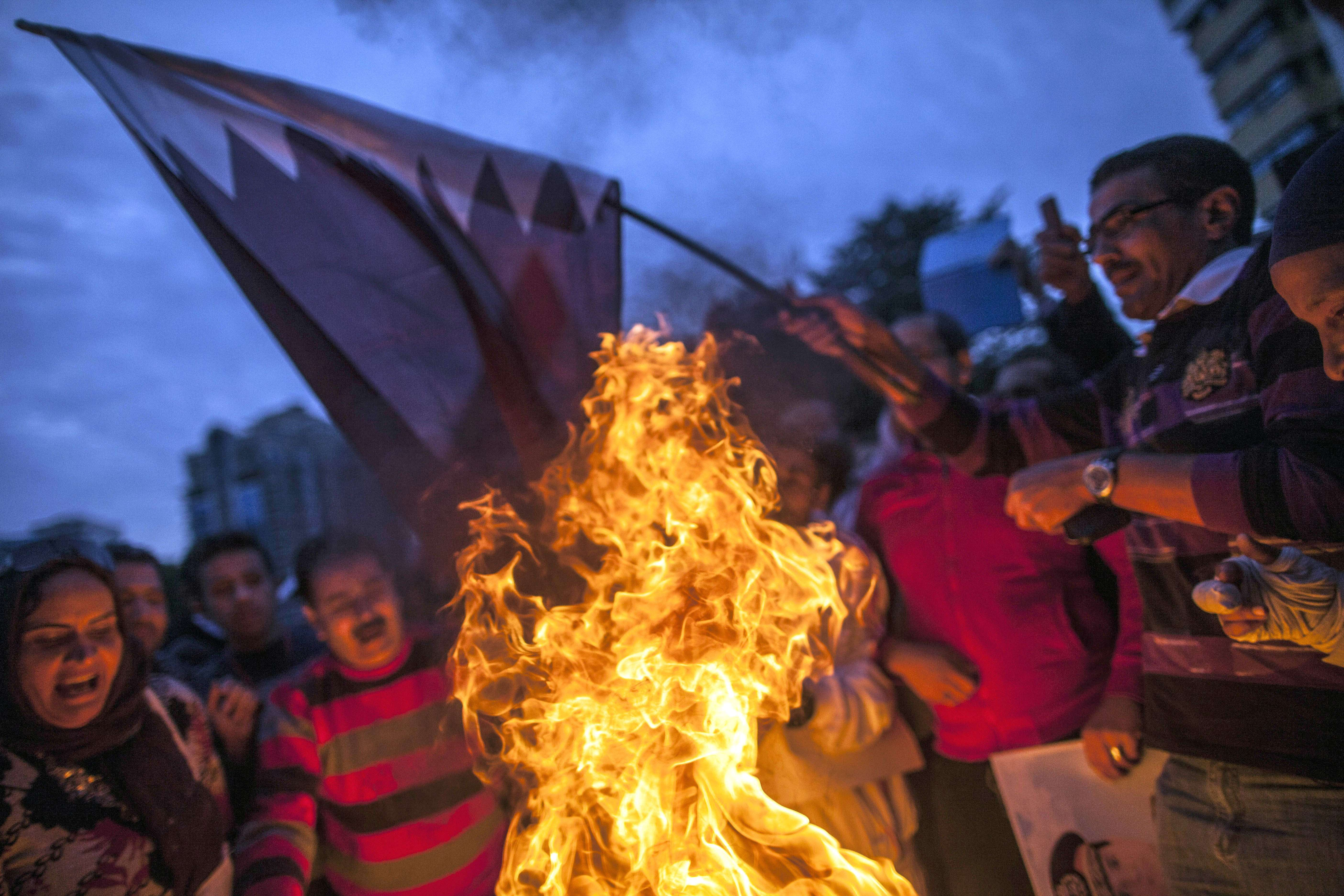 Supporters of Egypt's military chief Abdel Fattah al-Sisi burn a Qatari national flag during a demonstration outside the Qatari embassy in Cairo on November 30, 2013. (AFP PHOTO/MAHMOUD KHALED)