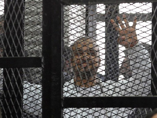 Egyptian Muslim Brotherhood senior member Mohamed Beltagy shows a four-finger sign, called Rabaa (four) in Arabic as he stands at the defendant's cage during his trial on 11 December 2013 (MAHER ISKANDER/AFP/Getty Images)