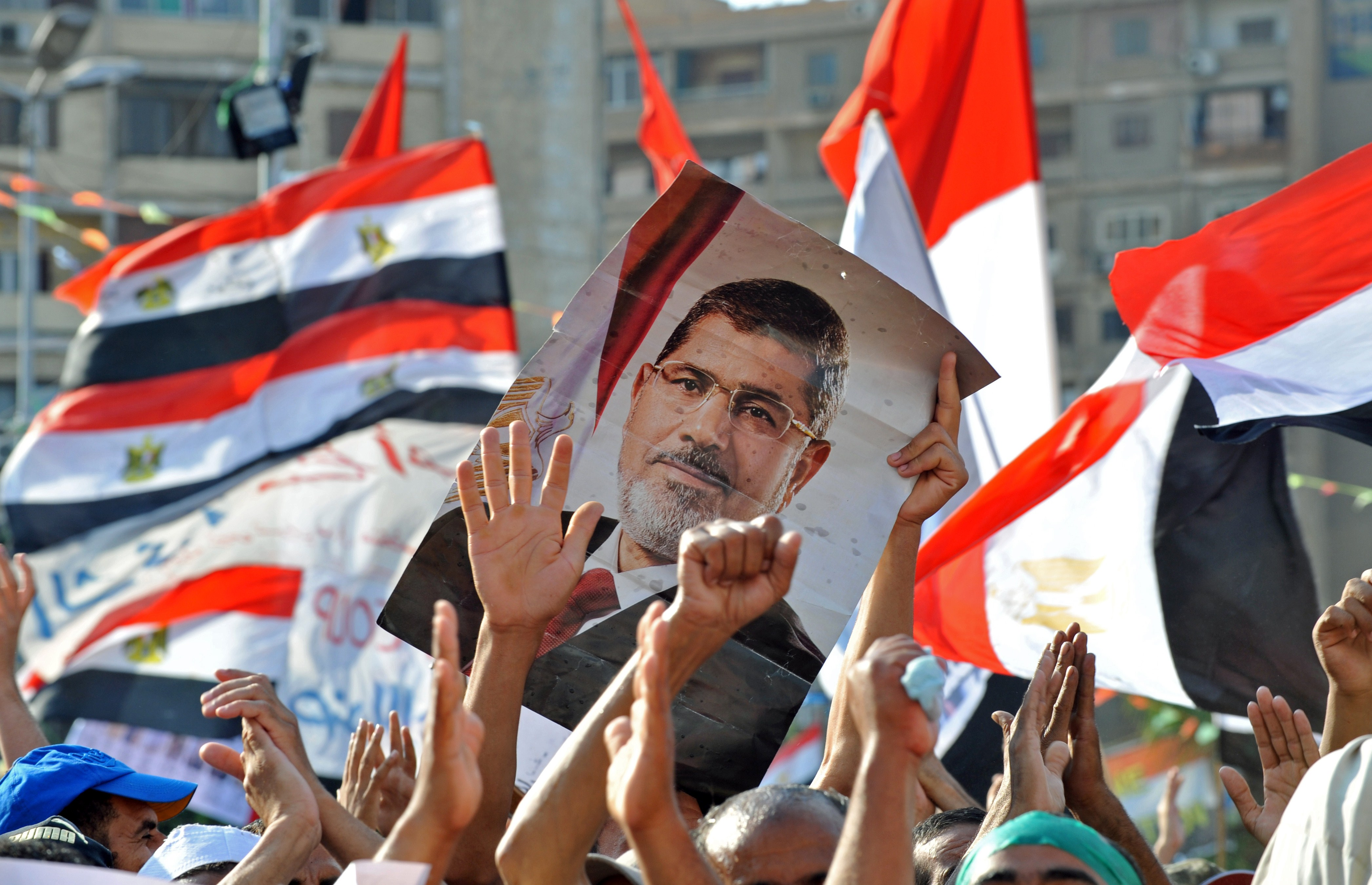 Egyptian supporters of deposed president Mohamed Morsi hold up his portrait and wave their national flag, as they continue to hold a sit in outside Cairo's Rabaa al-Adawiya mosque on July 24, 2013.  (AFP File Photo)