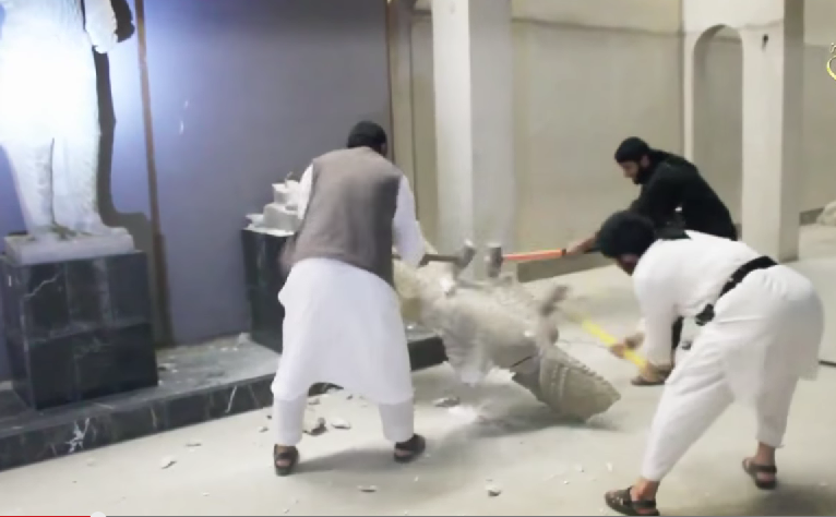 ISIS while destroying statues in Iraq (Photo from youtube)
