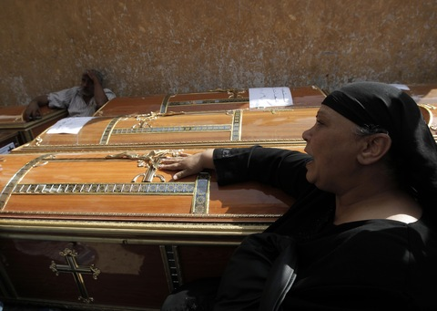 An Egyptian woman mourns over the coffins of some of the 24 Coptic Christians killed during Maspero massacre .  (Photo by Mahmud Hams/AFP/Getty Images)