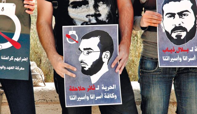 A protester holding a poster with the image of a Palestinian prisoner who is on hunger strike in an Israeli prison.  (AFP Photo)