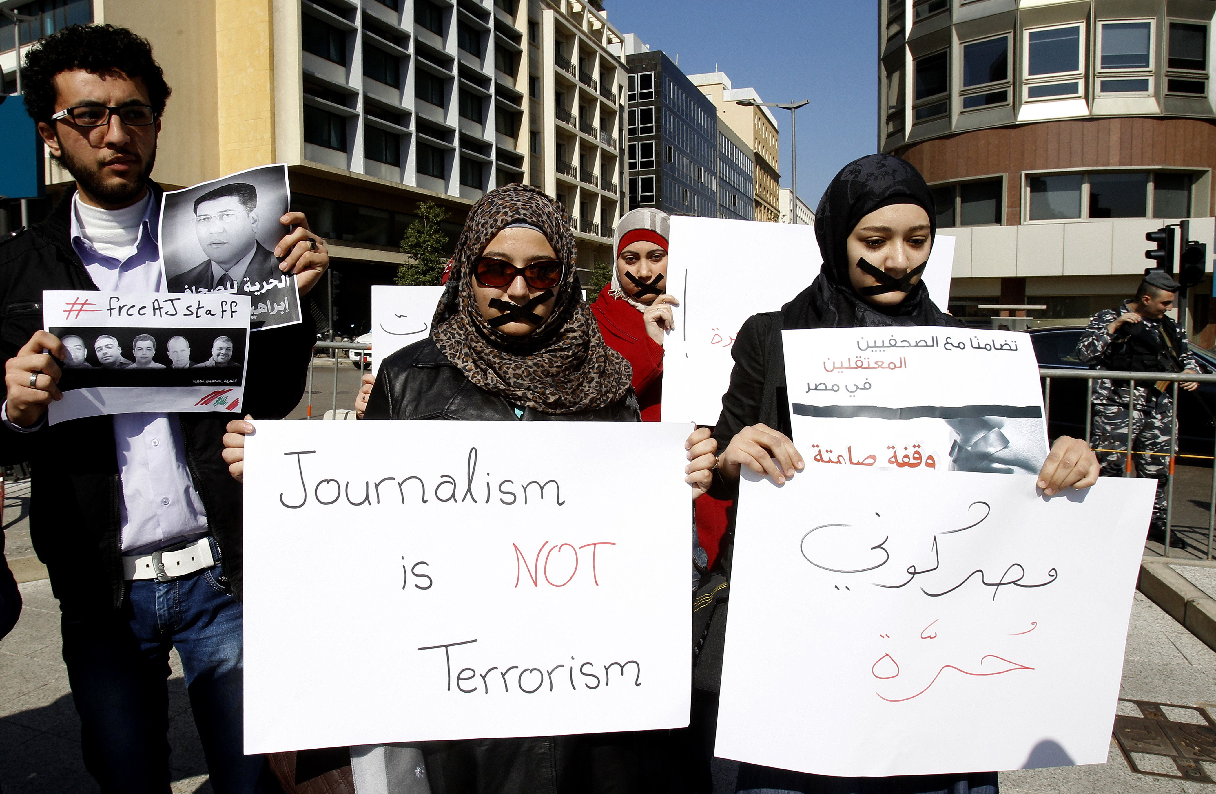 "Activists and journalists take part in a demonstration in support of the Al-Jazeera staff, who have been detained by Egyptian authorities since last year, in the Lebanese capital Beirut on February 8, 2014. Egyptian prosecutors on January 31 referred to trial 20 journalists allegedly working for Al-Jazeera after accusing them of portraying Egypt as being in a state of ""civil war"" and ""airing false news.""  (AFP PHOTO/ANWAR AMRO)"
