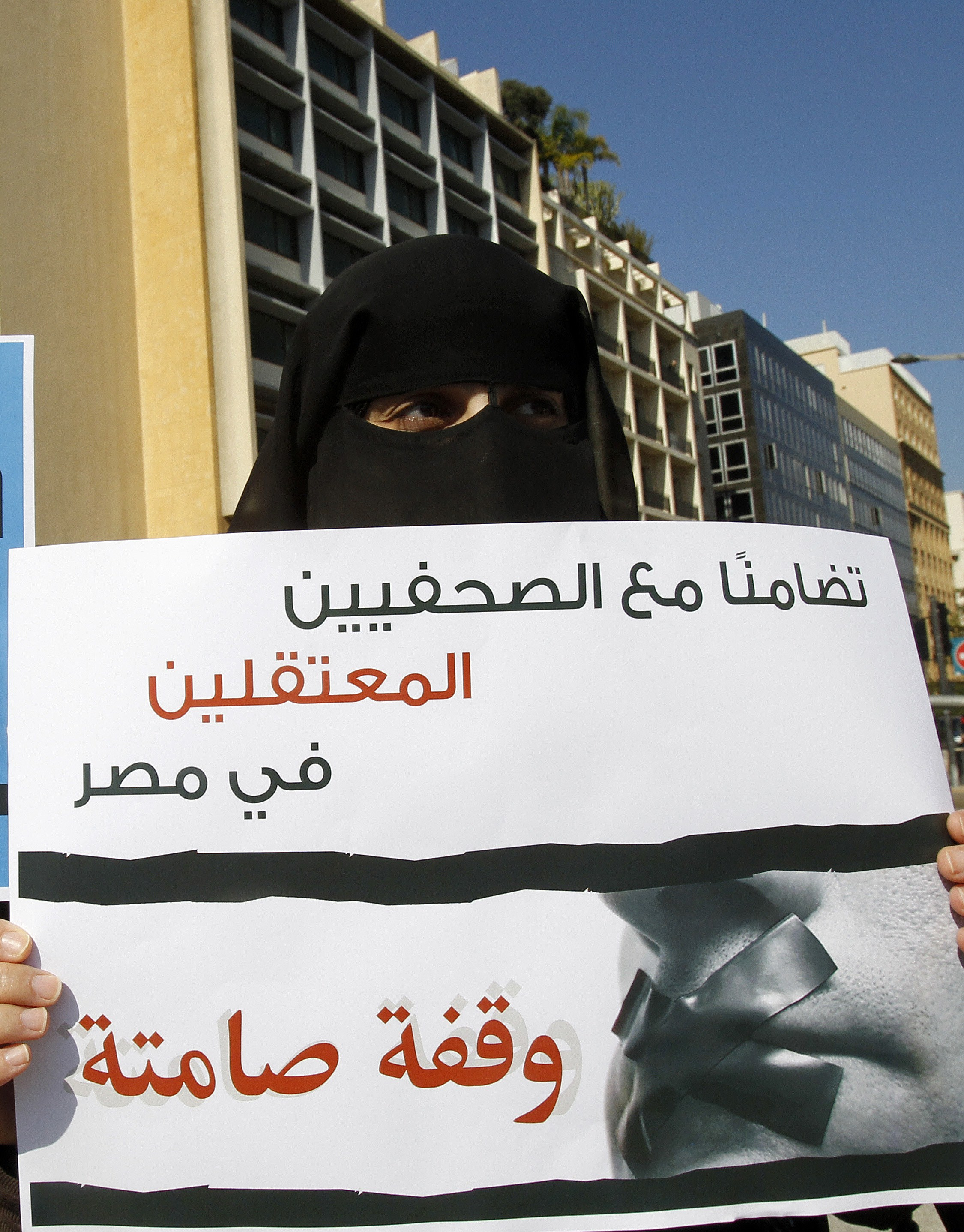 "An activist takes part in a demonstration in support of the Al-Jazeera staff, who have been detained by Egyptian authorities since last year, in the Lebanese capital Beirut on February 8, 2014. Egyptian prosecutors on January 31 referred to trial 20 journalists allegedly working for Al-Jazeera after accusing them of portraying Egypt as being in a state of ""civil war"" and ""airing false news.""  (AFP PHOTO/ANWAR AMRO)"