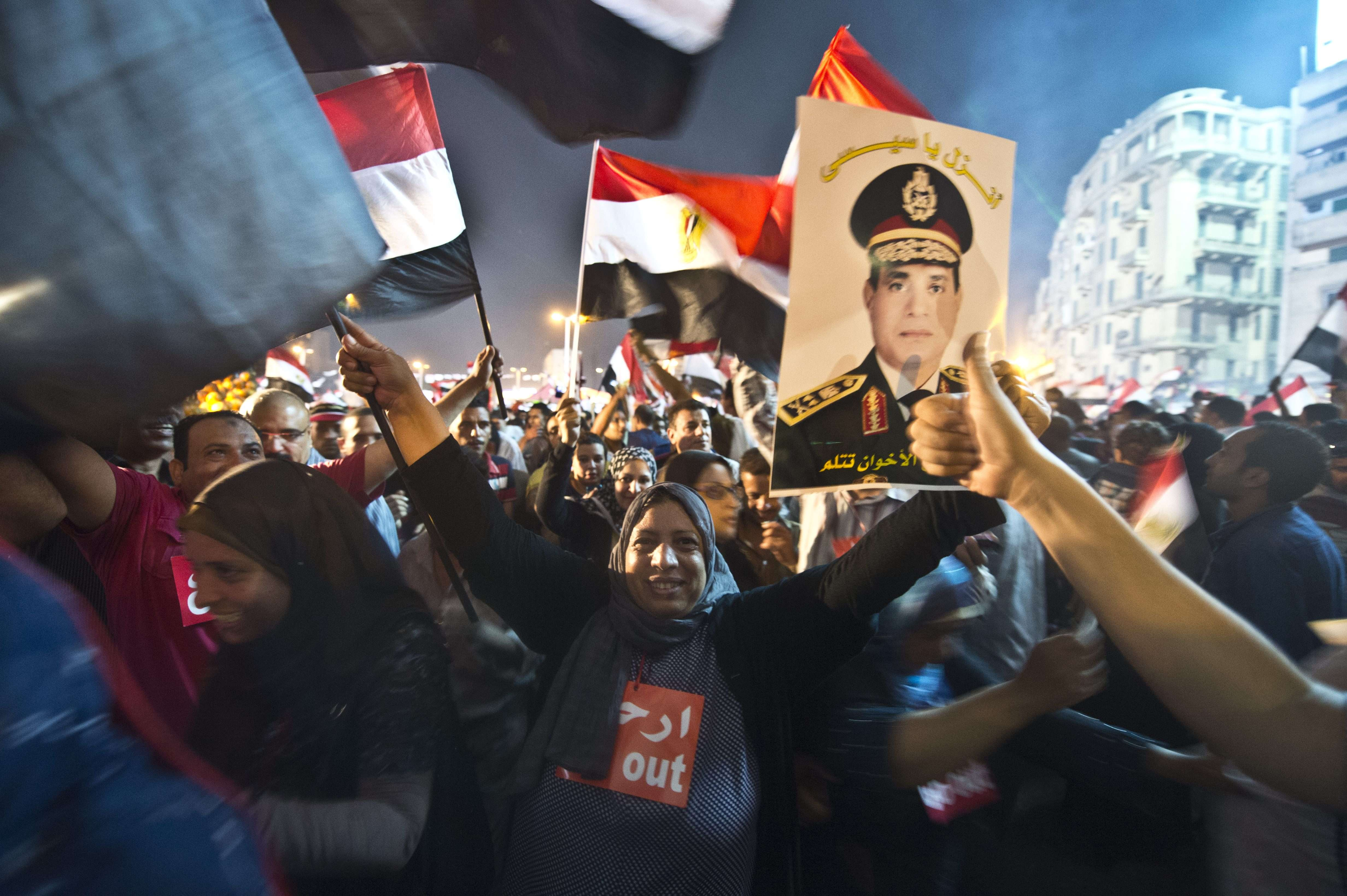 People celebrate at Tahrir Square with a portrait of Army chief Abdel Fattah al-Sisi after a broadcast confirming that the army will temporarily be taking over from the country's first democratically elected president Mohammed Morsi on July 3, 2013 in Cairo.  (AFP Photo)