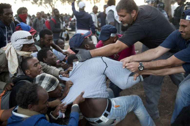 Israeli policemen and immigration officers raid a protest camp set up by African asylum seekers near a border crossing with Egypt in the Negev Desert on June 29, 2014.  (AFP Photo/ Oren Ziv)