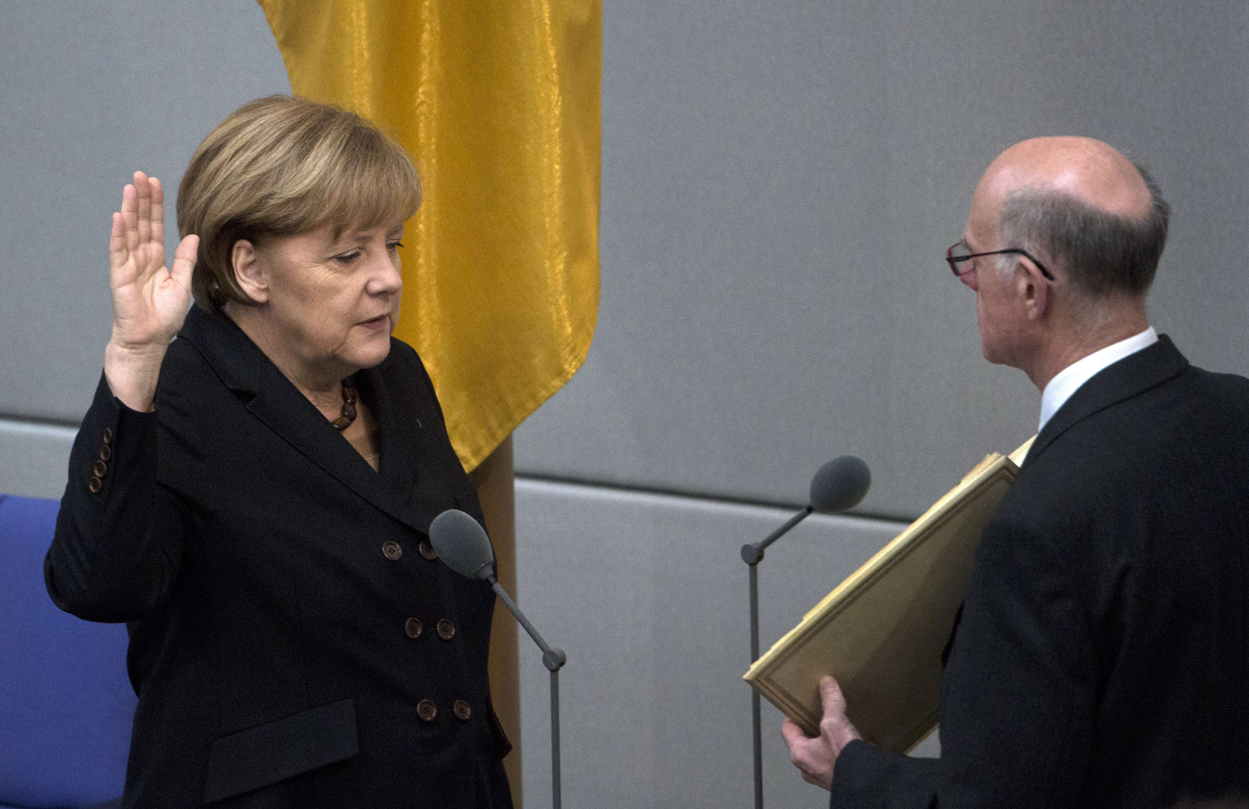 German Chancellor Angela Merkel is sworn in by the President of the Parliament Norbert Lammert (R) at the Bundestag (lower house of parliament) on December 17, 2013 in Berlin.  AFP PHOTO / JOHANNES EISELE