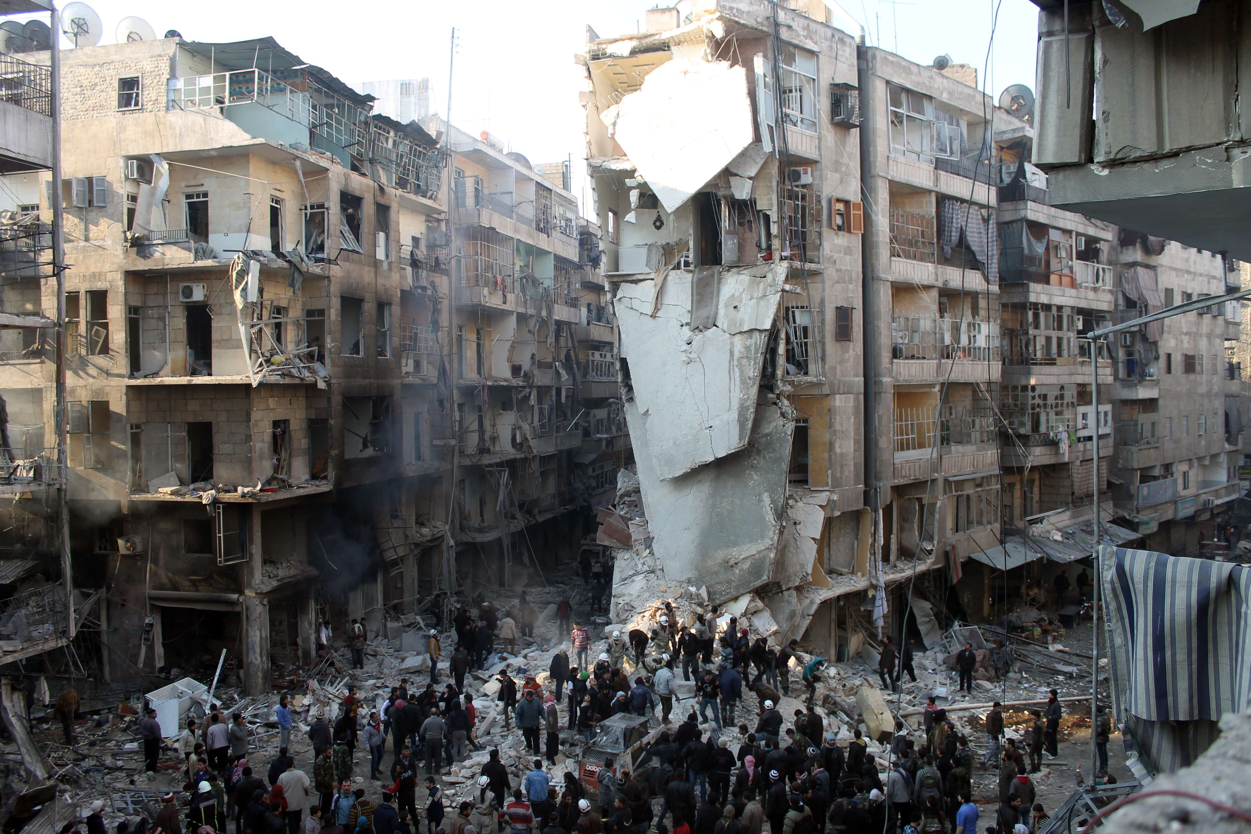 Syrians search for survivors amidst the rubble following an airstrike in the Shaar neighborhood of Aleppo on December 17, 2013.  (AFP PHOTO/MOHAMMED AL-KHATIEB)