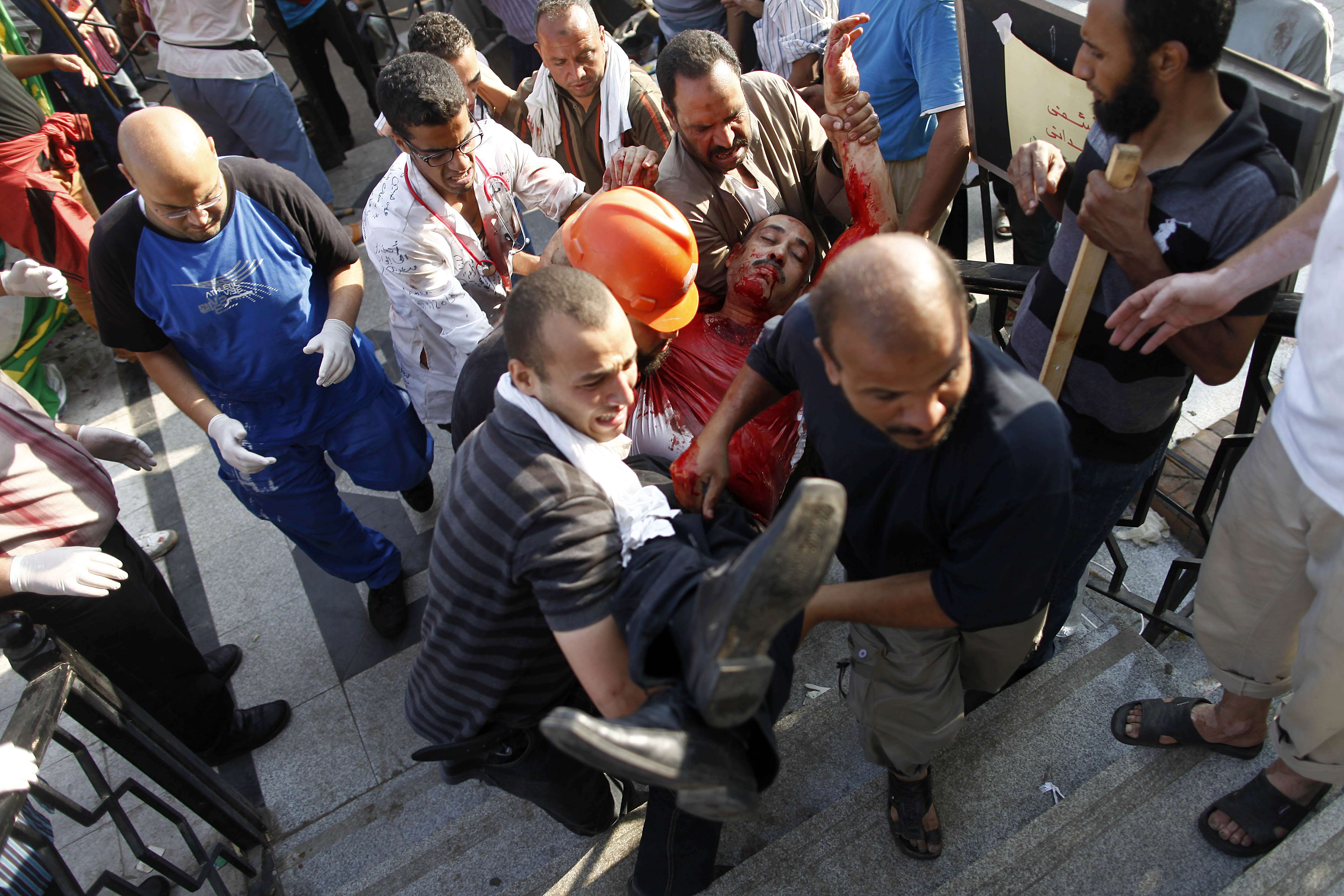 A supporter of the Muslim Brotherhood who was injured during a rally in support of deposed president Mohamed Morsi is carried to safety following clashes with police outside the elite Republican Guards base in Cairo early on July 8, 2013.  (AFP Photo)