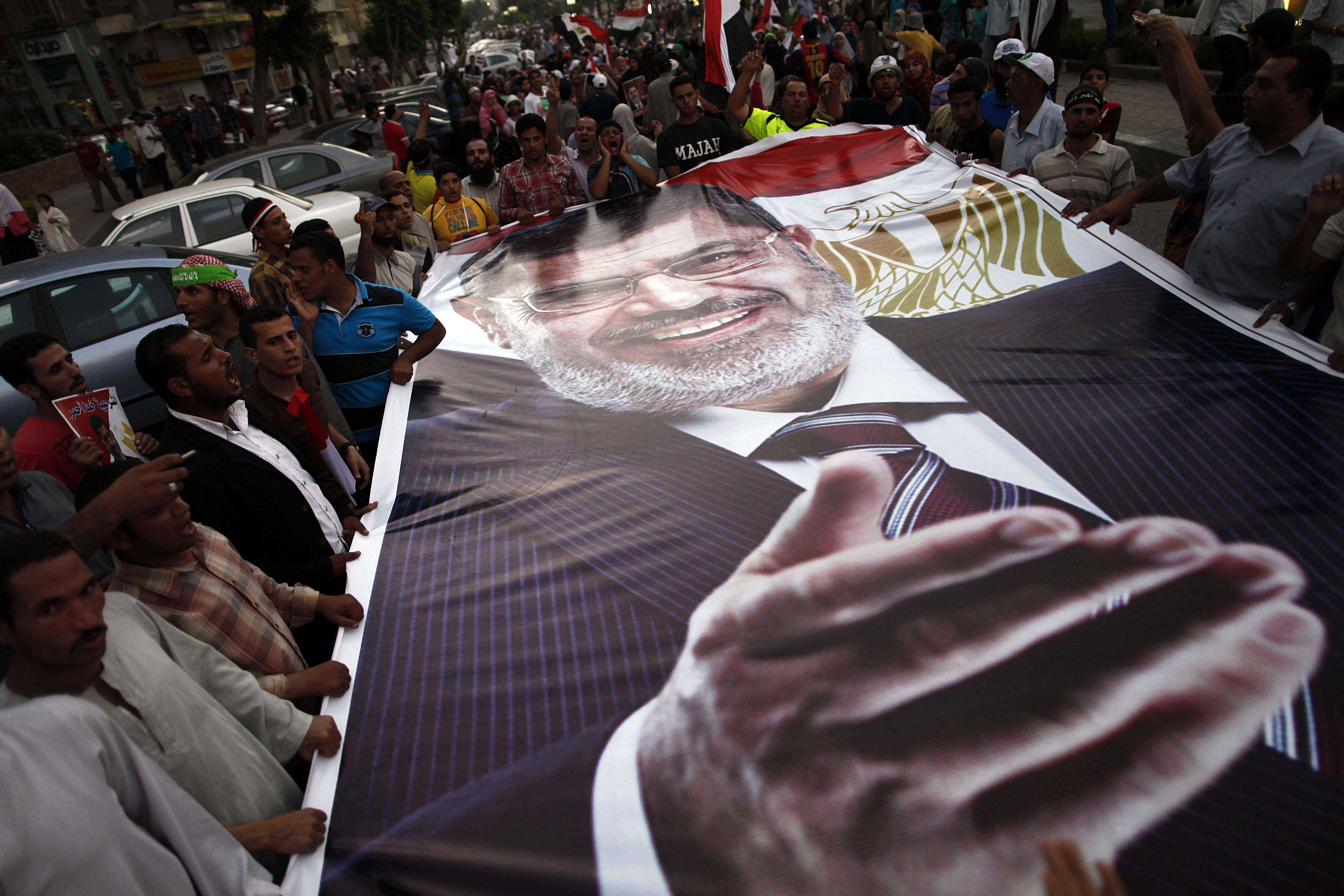 Ousted President Mohamed Morsi supporters and Muslim Brotherhood members hold a giant portrait of him as they demonstrate against his toppling at Raba al-Adwyia mosque on July 7, 2013 in Cairo. (AFP Photo)