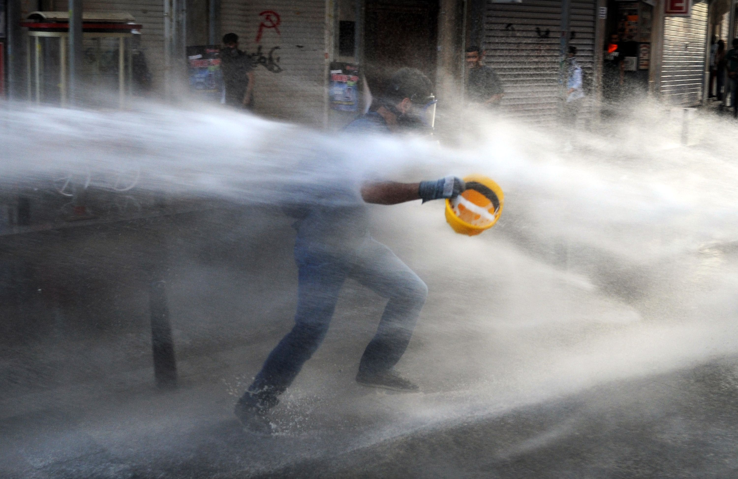 A protestor runs as police used water cannon during clashes on Istiklal avenue, in Istanbul on July 8, 2013.  (AFP Photo)