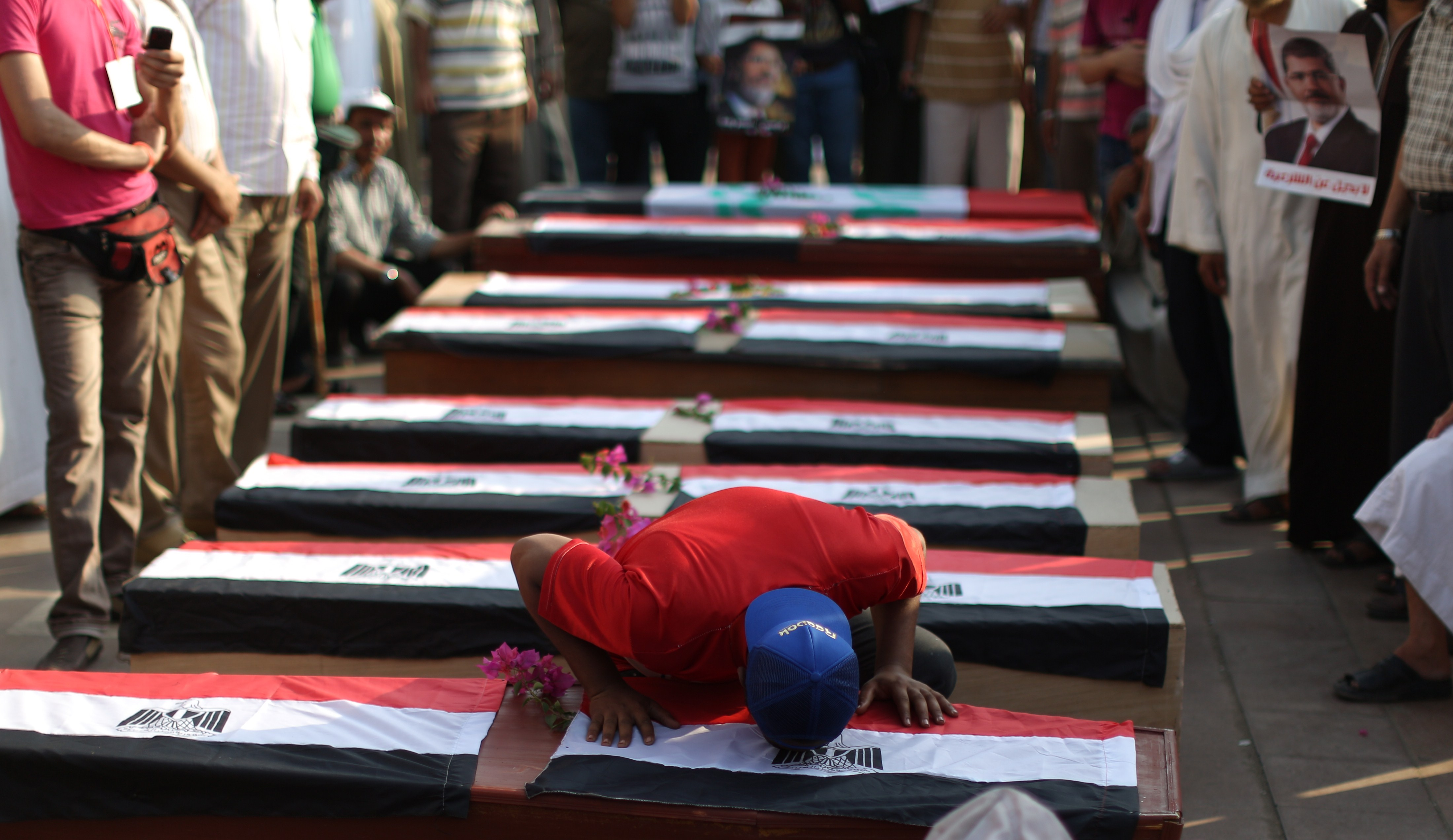 supporter of deposed Egyptian president Mohamed Morsi kisse an empty coffins during a fake funeral in the memory of their fellow protesters who died during clashes the day before, on July 9, 2013 as part of a rally in support with Morsi in front of Cairo's Rabaa al-Adawiya mosque.  (AFP Photo)