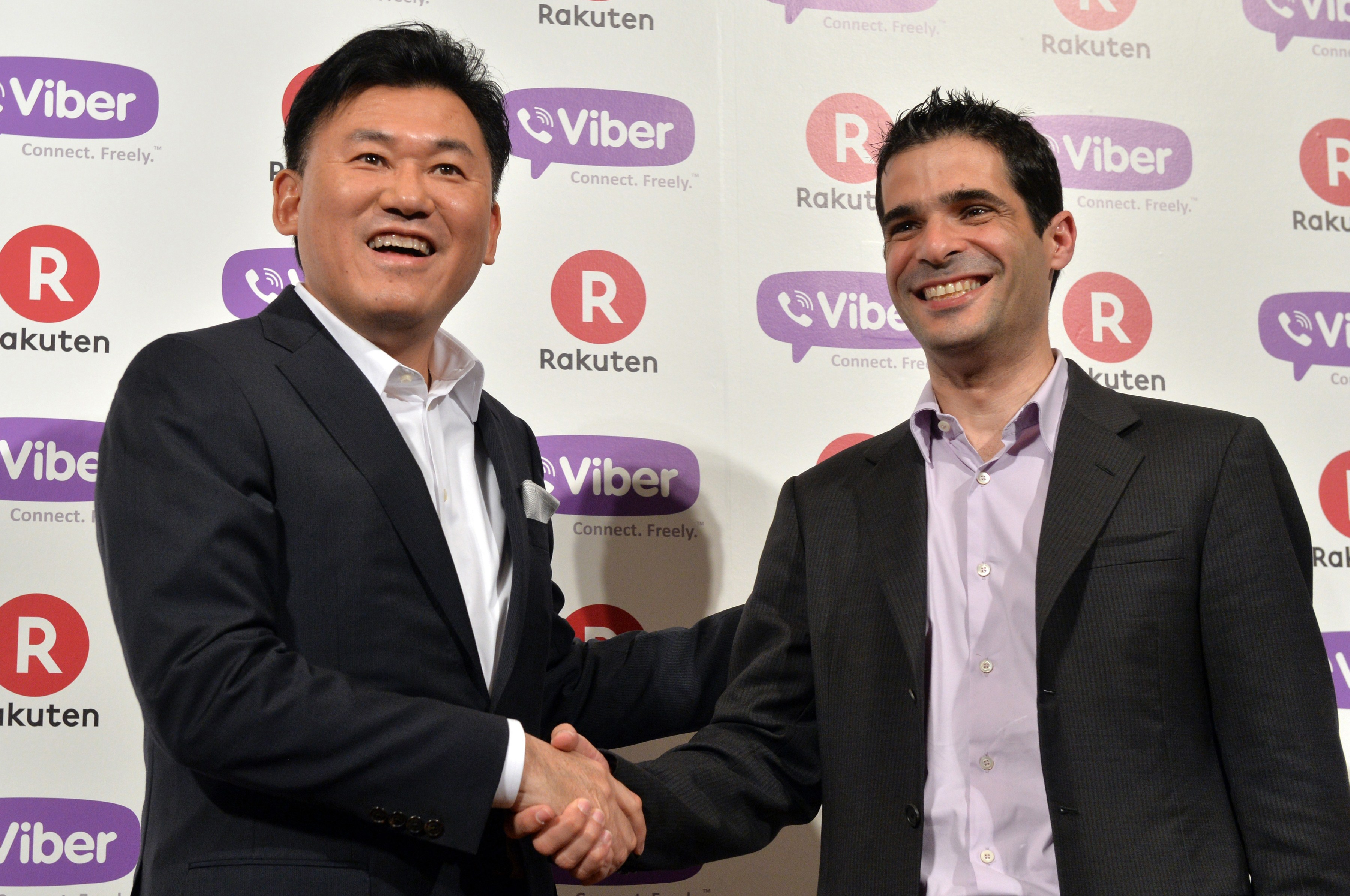 Japan's online shopping giant Rakuten president Hiroshi Mikitani (L) shakes hands with Cyprus-based application maker Viber Media CEO Talmon Marco in Tokyo on February 14, 2014.  Rakuten, Japan's largest online shopping mall operator, said on February 14 it would buy Cyprus-based application maker Viber Media for 900 million USD, as its expands an overseas empire that includes Canadian e-reader company Kobo.   AFP PHOTO / Yoshikazu TSUNO